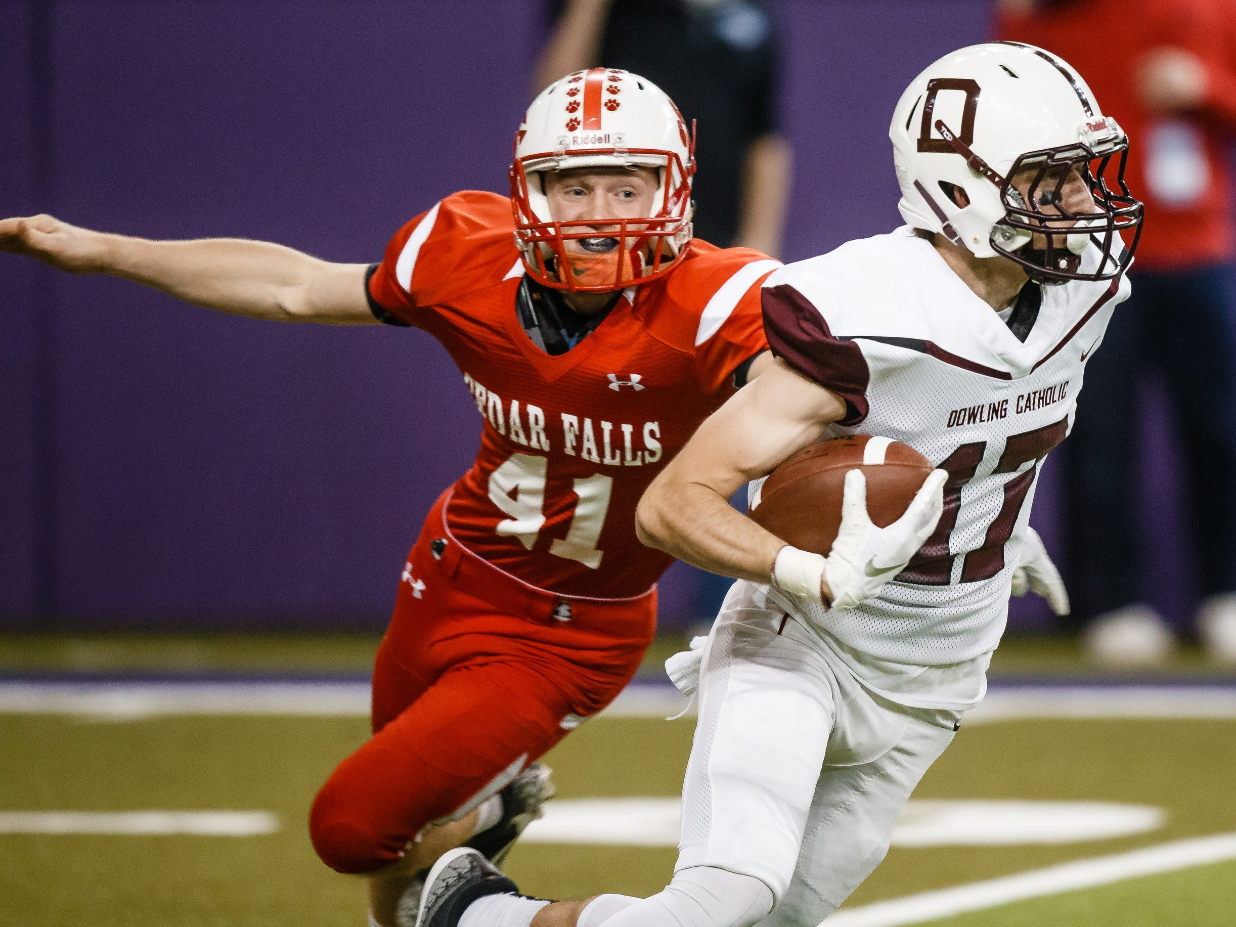 Dowling Catholic's Matt Stilwill (17) is chased by Cedar Falls's Austin Cross (41) during their class 4A state championship football game on Friday, Nov. 16, 2018, in Cedar Falls. Cedar Falls takes a 13-7 lead into halftime.