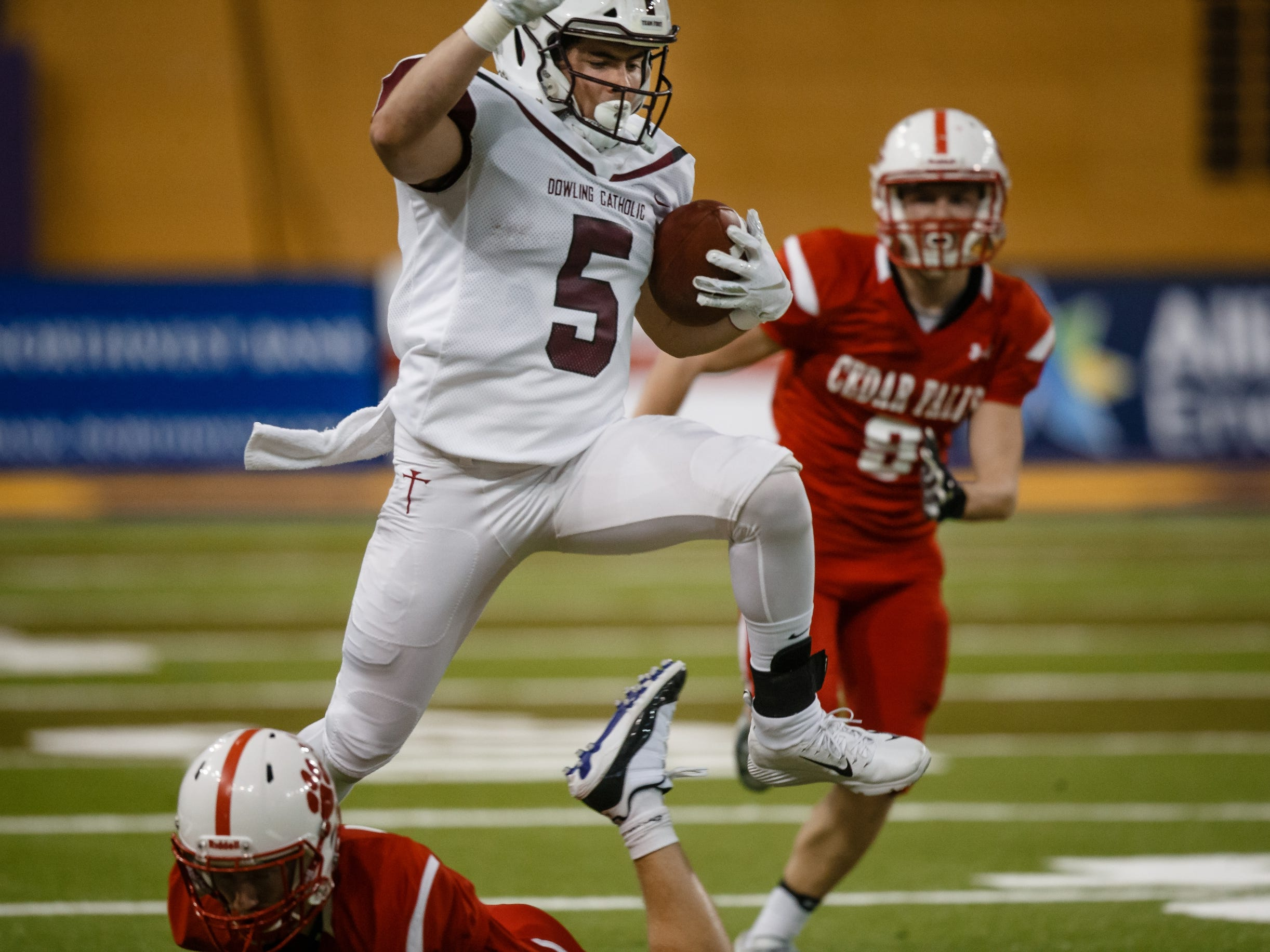 Dowling Catholic's Collin Cook (5) jumps over a defender during their class 4A state championship football game against Cedar Falls on Friday, Nov. 16, 2018, in Cedar Falls. Cedar Falls takes a 13-7 lead into halftime.