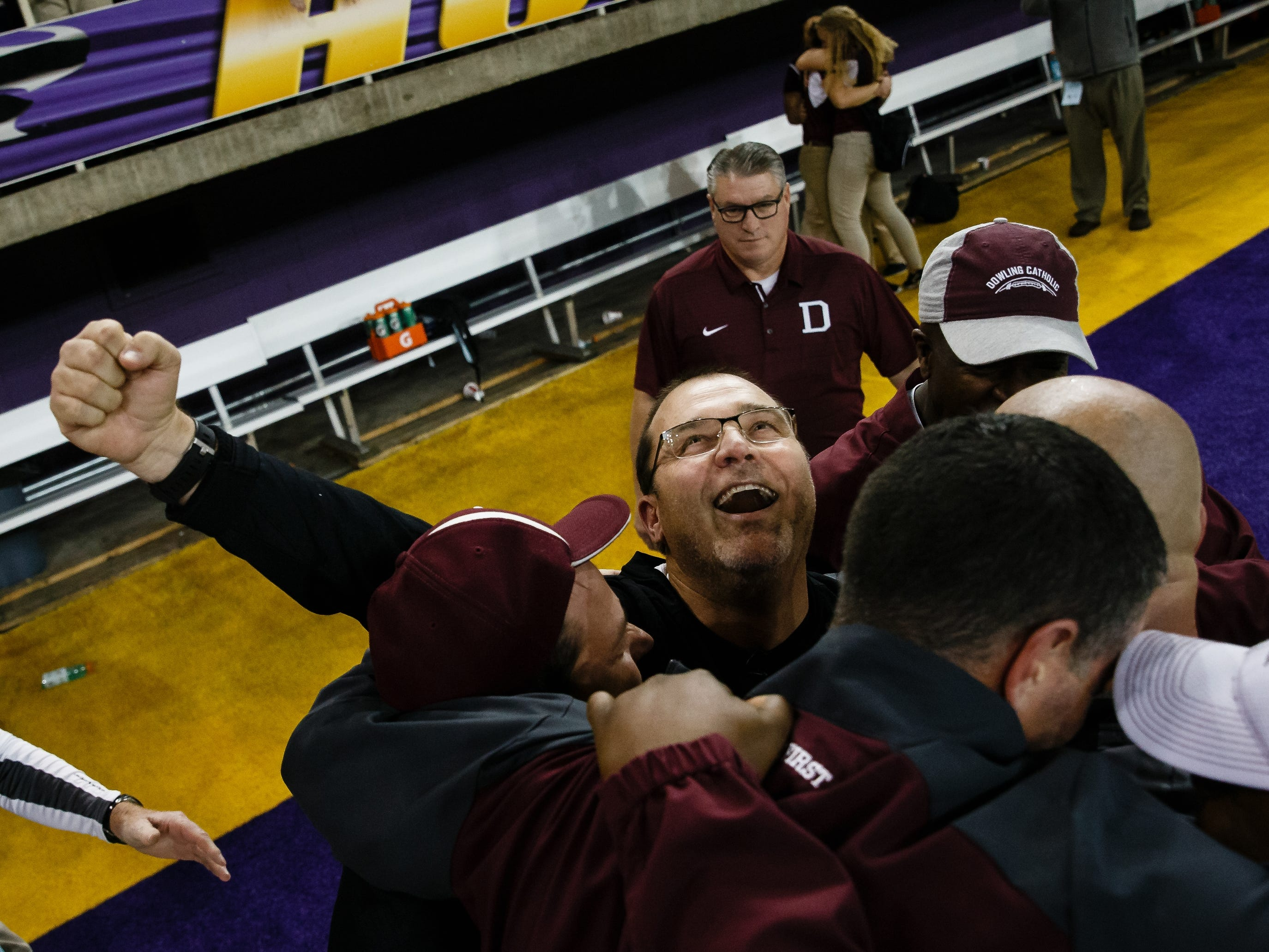 The Dowling Catholic coaching staff including head coach Tom Wilson, center, celebrate their teams 22-16 win over Cedar Falls during their class 4A state championship football game on Friday, Nov. 16, 2018, in Cedar Falls.
