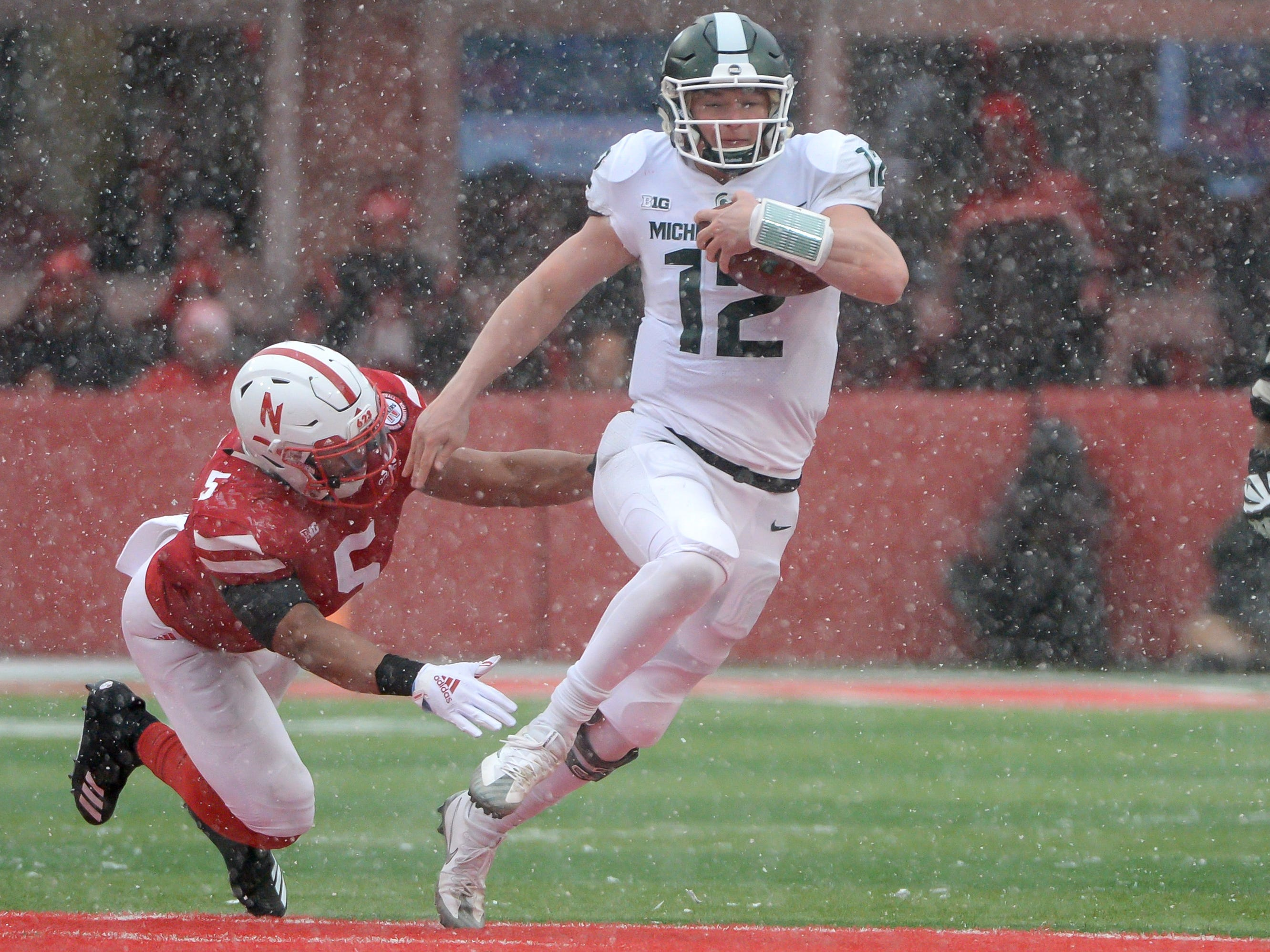 Michigan State quarterback Rocky Lombardi runs from Nebraska linebacker Dedrick Young II in the second half at Memorial Stadium on Nov. 17, 2018 in Lincoln, Neb.