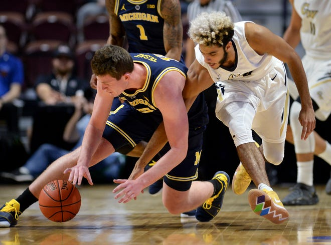 Michigan's Jon Teske steals the ball from George Washington's Justin Mazzulla in the second half Saturday.