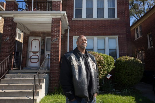 Karl Henderson, 54, poses outside of his home on Thursday, Oct. 18, 2018 in Detroit. Henderson and his fiancé didn't know that the home they have been renting for years was scheduled for foreclosure. The United Community Housing Coalition or UCHC placed the home in the buy back program and gave Karl Henderson a loan to be able to buy the deed to the house.