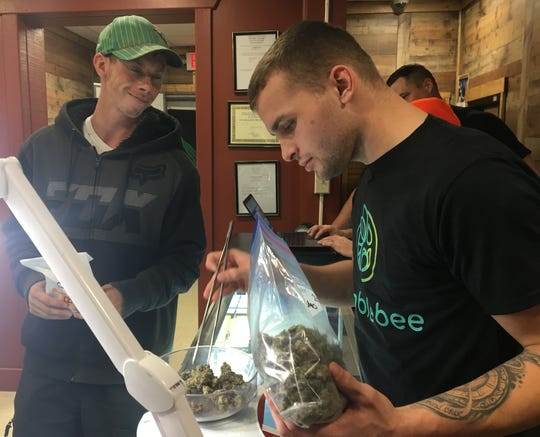 (l to r) Jordan Villeme, 22, budtender from Gaylord, works as customer Michael Kaiser, 32,  Gaylord looks on at HumbleBee Products medical marijuana dispensary and processor in the northwest Michigan town of Frederic. They are the first dispensary to be licensed in northern lower Michigan.