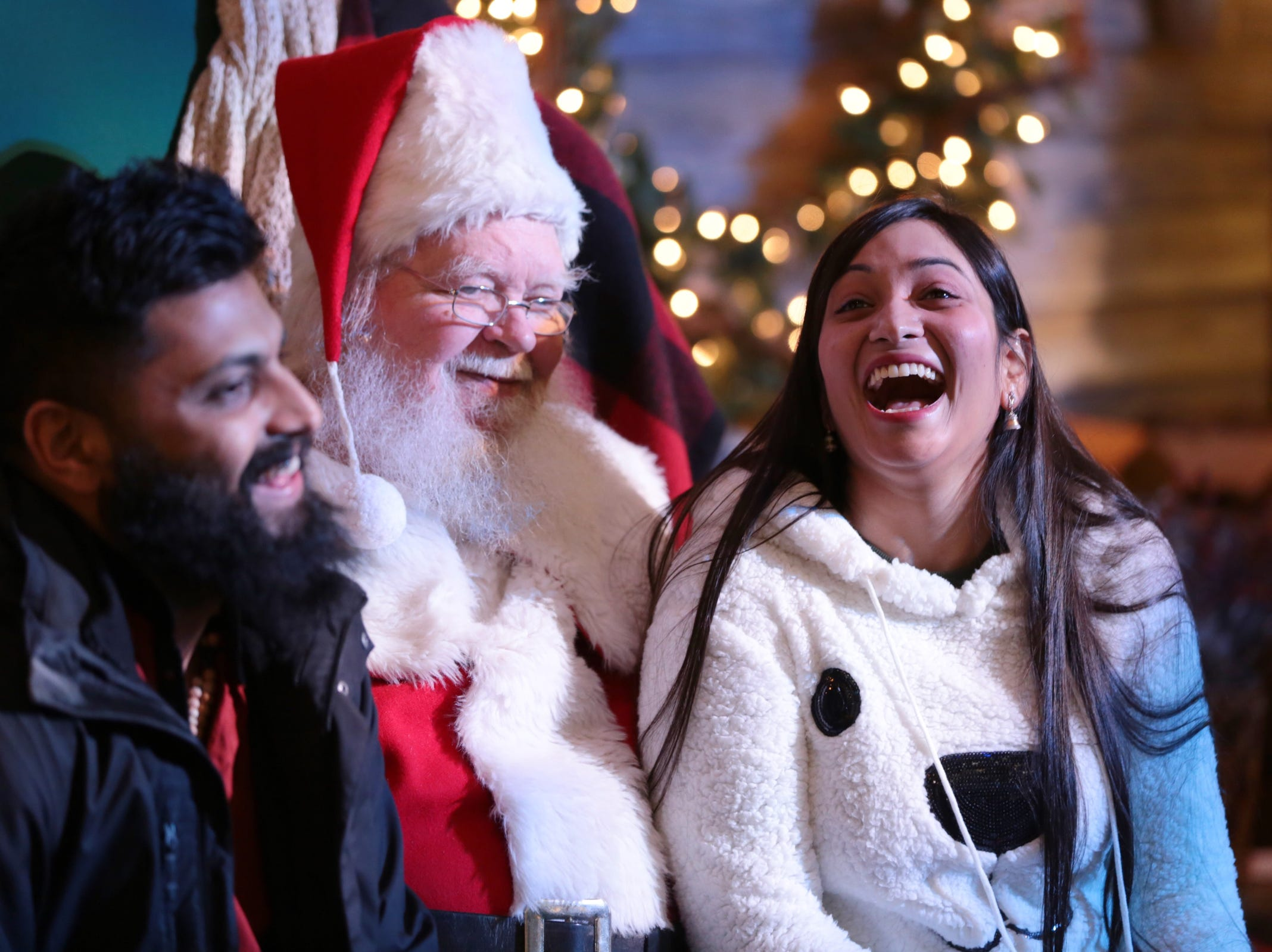 Sachin Puthur (left) of Detroit and Sheenam Gupta of Dallas, TX sit with Santa Claus inside One Campus Martius during the annual tree lighting event at Campus Martius Park in downtown Detroit on Friday, November 16, 2018.