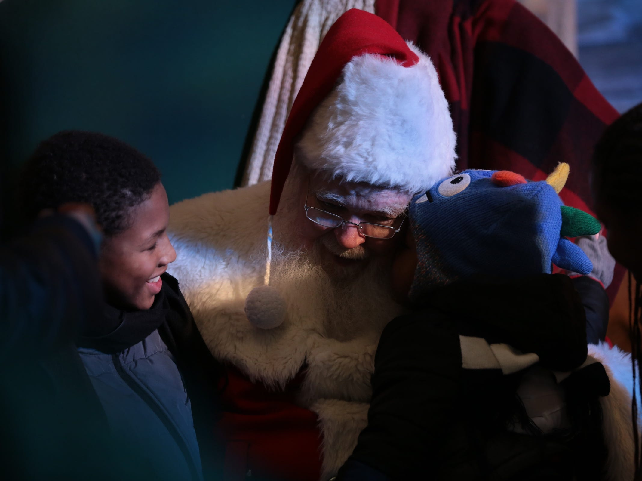 Cameron Hurst of Eastpointe whispers to Santa Claus while sitting with his brother Christian Hurst of Eastpointe inside One Campus Martius during the annual tree lighting event at Campus Martius Park in downtown Detroit on Friday, November 16, 2018.