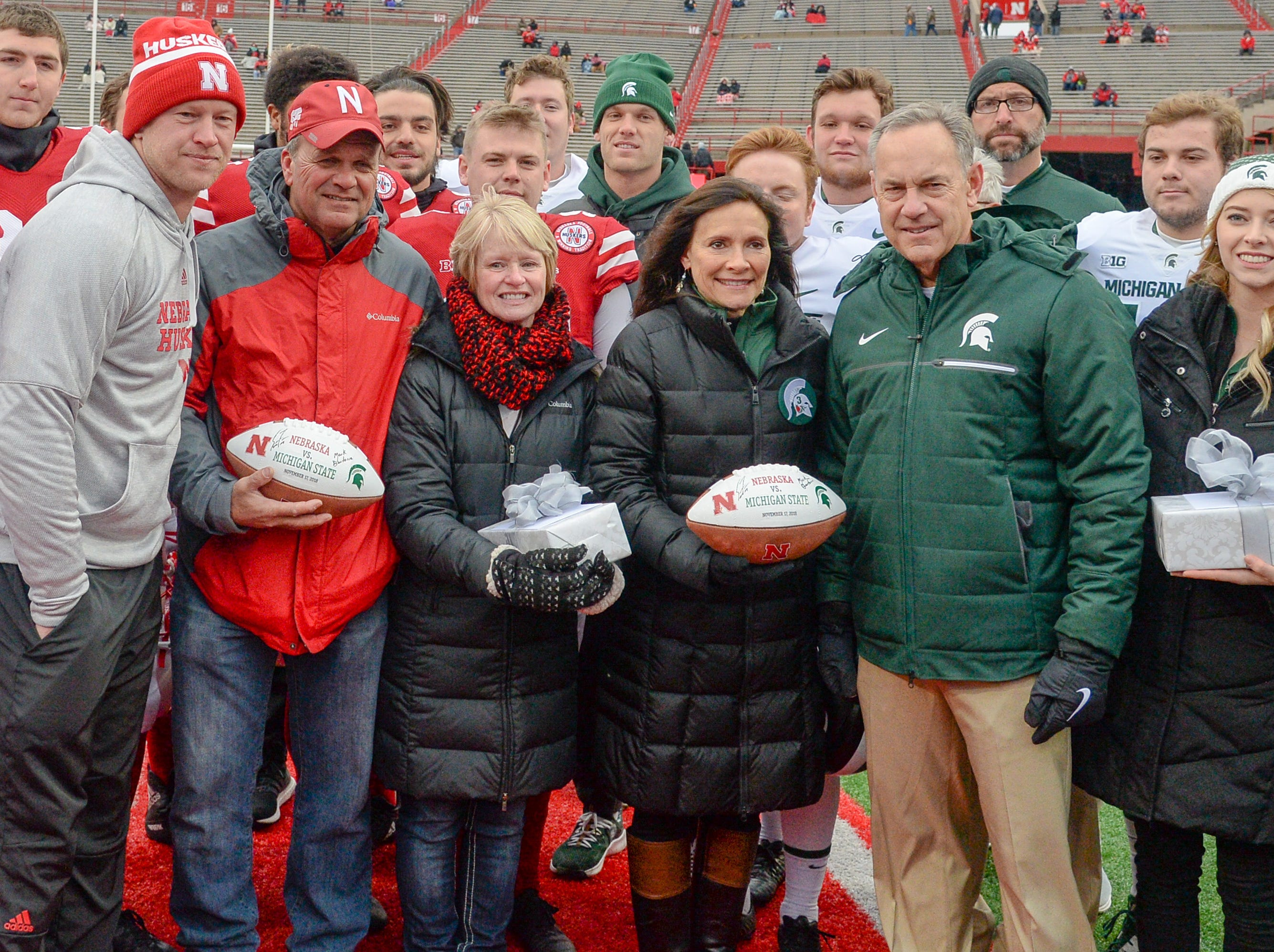 (From left) Nebraska coach Scott Frost and Gerald and Jill Foltz, parents of the deceased kicker Sam Foltz, and Michigan State coach Mark Dantonio and Karen Sadler and Katie Sadler, mother and sister of deceased kicker Mike Sadler, meet on the field for a ceremony before the game on Saturday, Nov. 17, 2018, in Lincoln, Neb.