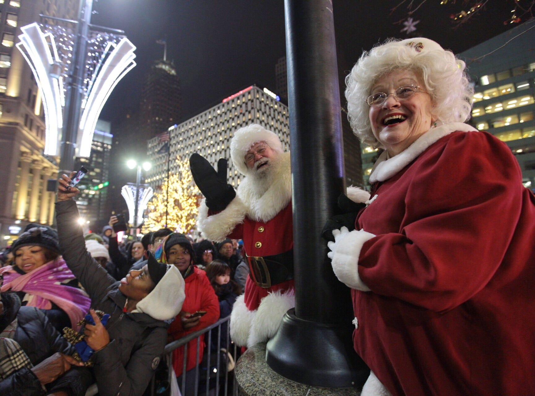 Santa Claus and Mrs. Claus wave to the crowd gathered during the annual tree lighting event at Campus Martius Park in downtown Detroit on Friday, November 16, 2018.