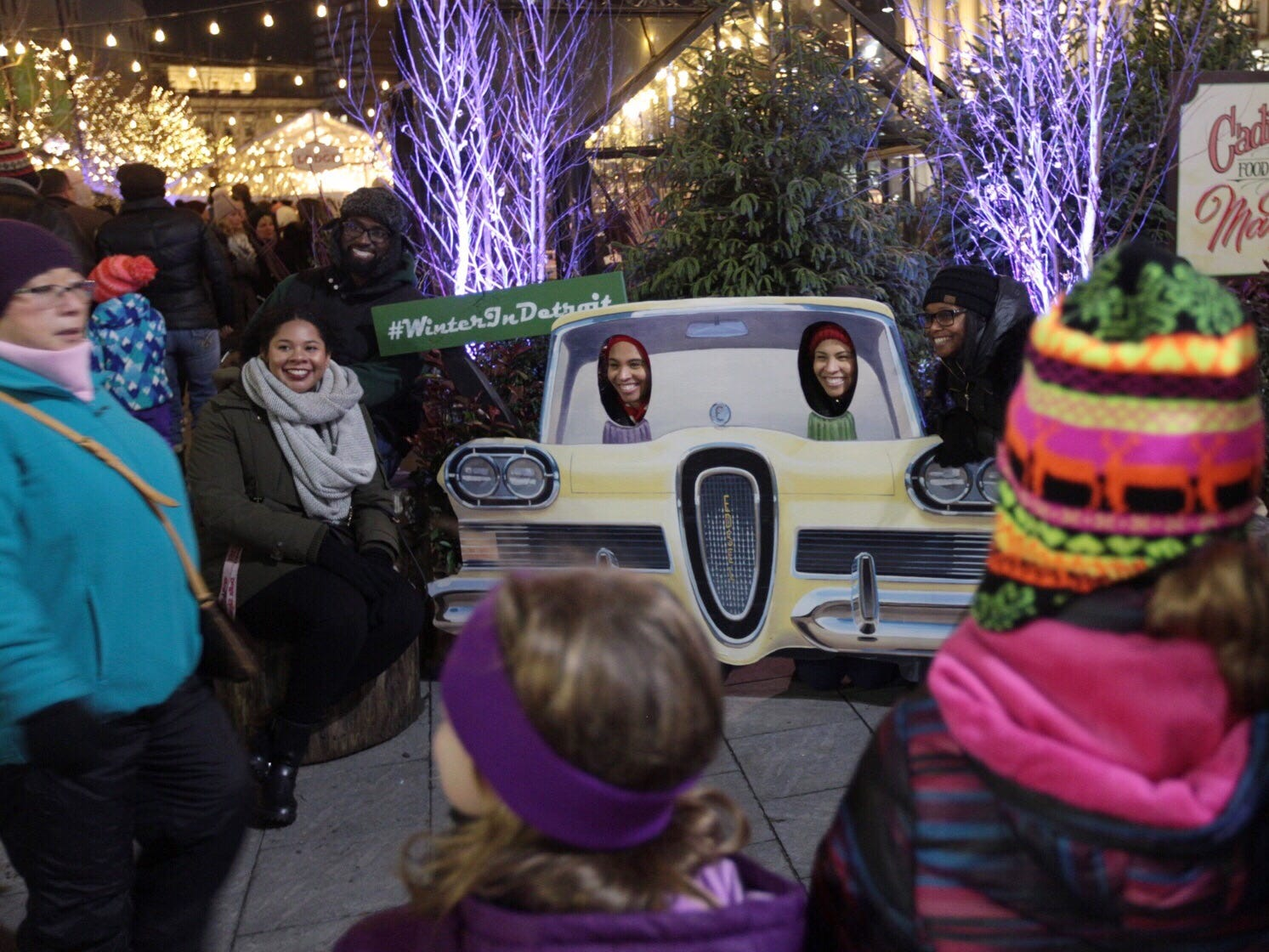 People pose for a photo in cutouts during the annual tree lighting event at Campus Martius Park in downtown Detroit on Friday, November 16, 2018.