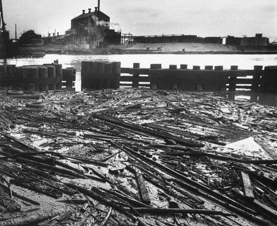 Boards, dead fish and other debris lay in an oil slick trapped behind bridge pilings near mouth of Rouge River that feeds into the Detroit River in Detroit on May 22, 1969. The General Chemical plant can be seen from this Zug Island bridge area.
