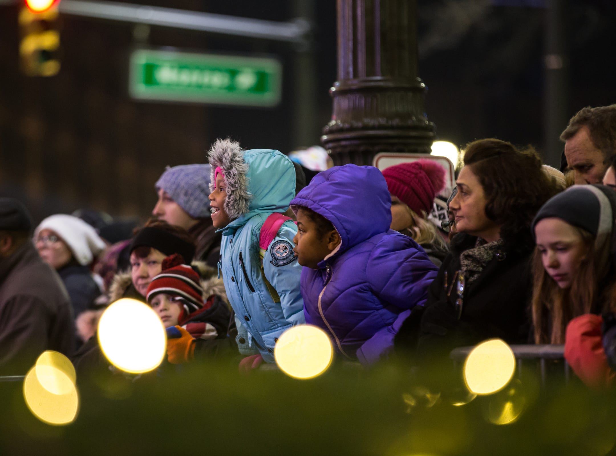 People line along the gates to watch a performance during the annual tree lighting event at Campus Martius Park in downtown Detroit on Friday, November 16, 2018.