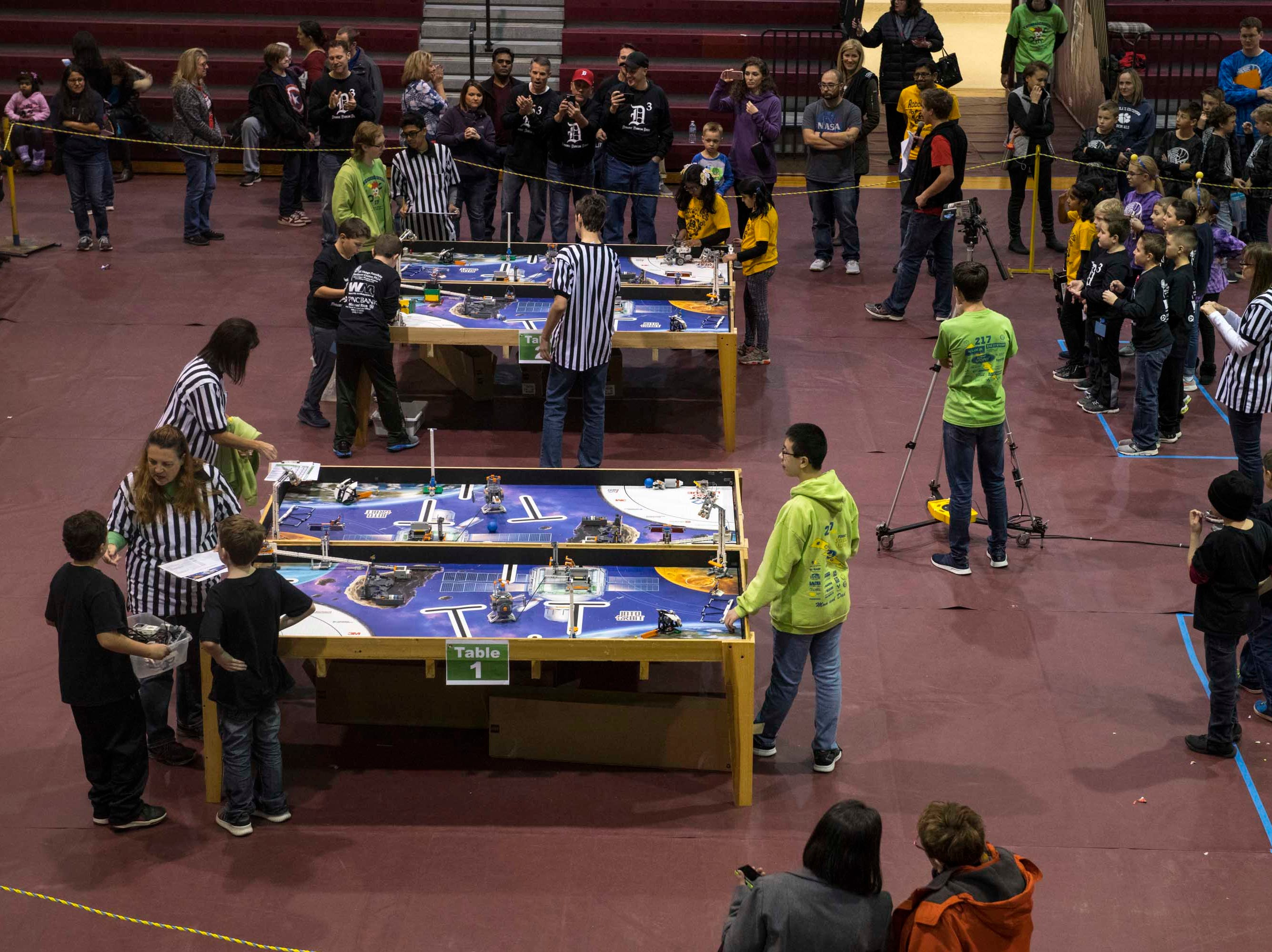 Teams come together with their LEGO robots as coaches, parents, and fans watch from the sidelines.