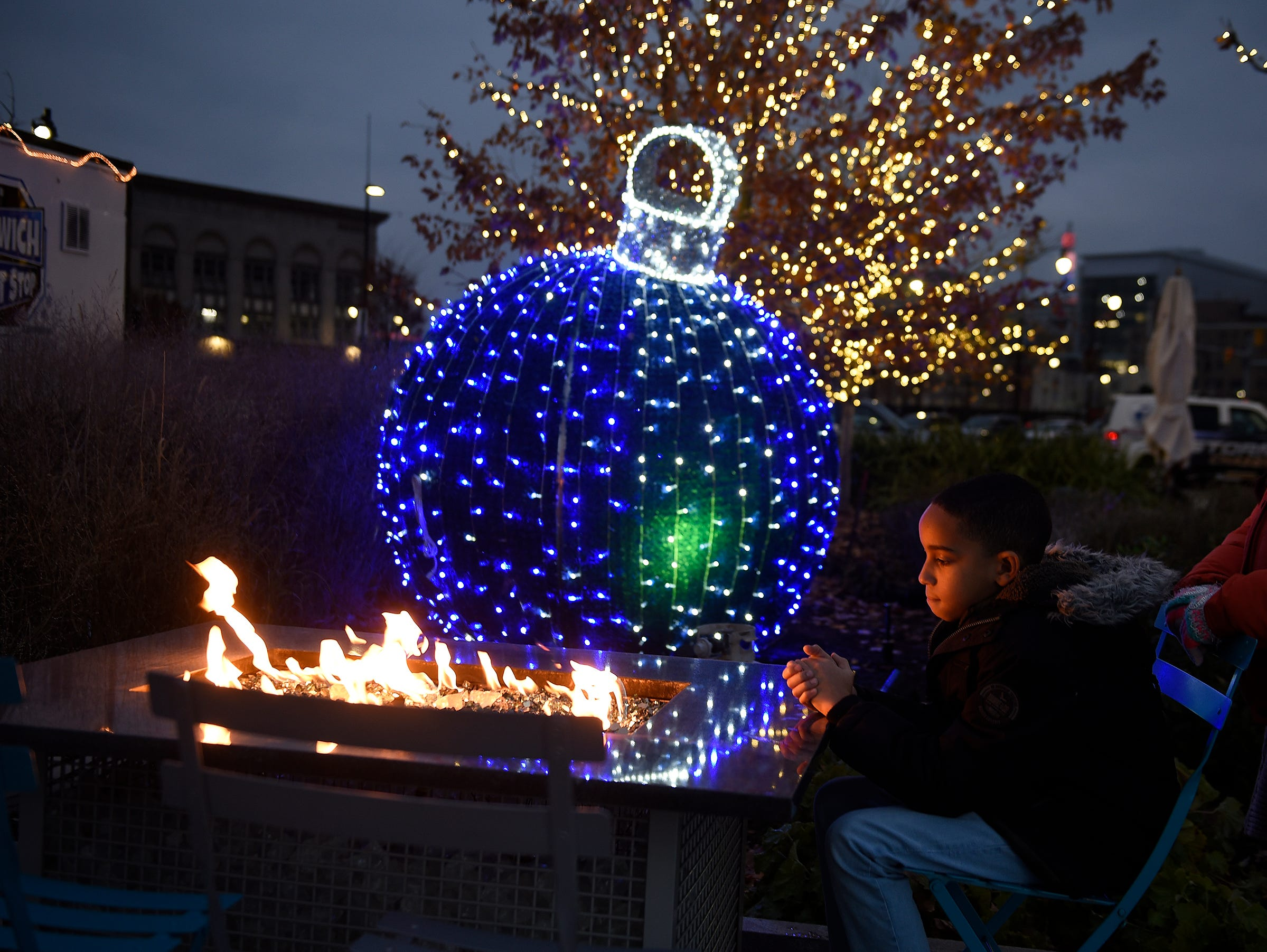 Aiden Black, 9, of Taylor warms his hands near the open fire pit at Beacon Park.
