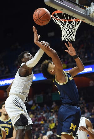 George Washington's Terry Nolan Jr. fouls Michigan's Jordan Poole in the first half.