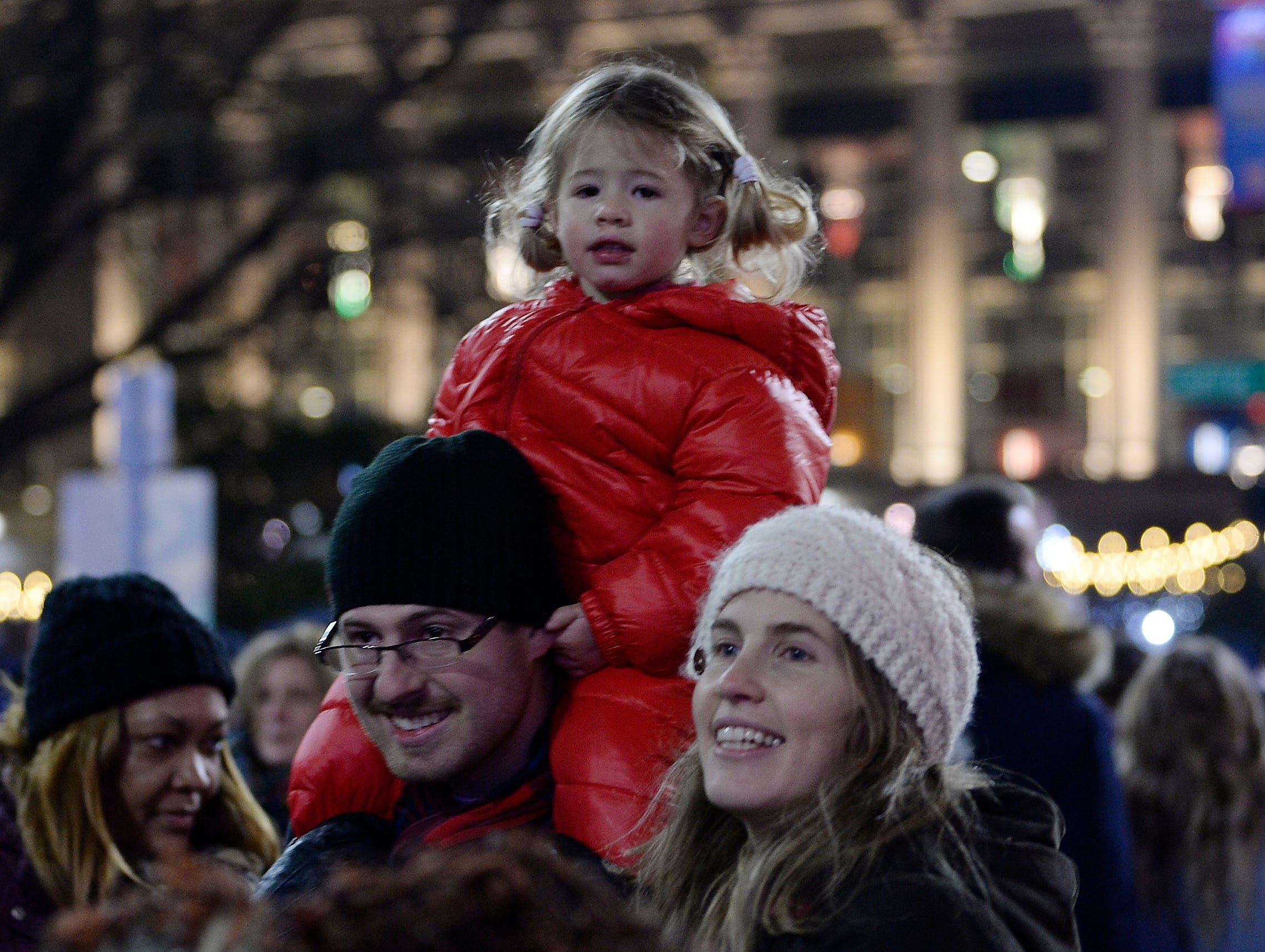 Emma Olney, 2, of Grosse Pointe Farms enjoys the view from dad Stewart Olney's shoulders during the tree lighting ceremony. Her mom, Elizabeth Olney, is to the right.