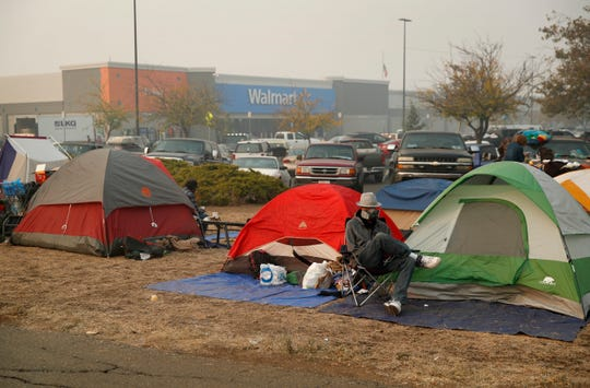People sit by their tents at a makeshift encampment outside a Walmart store for people displaced by the Camp Fire, Friday, Nov. 16, 2018, in Chico, Calif.