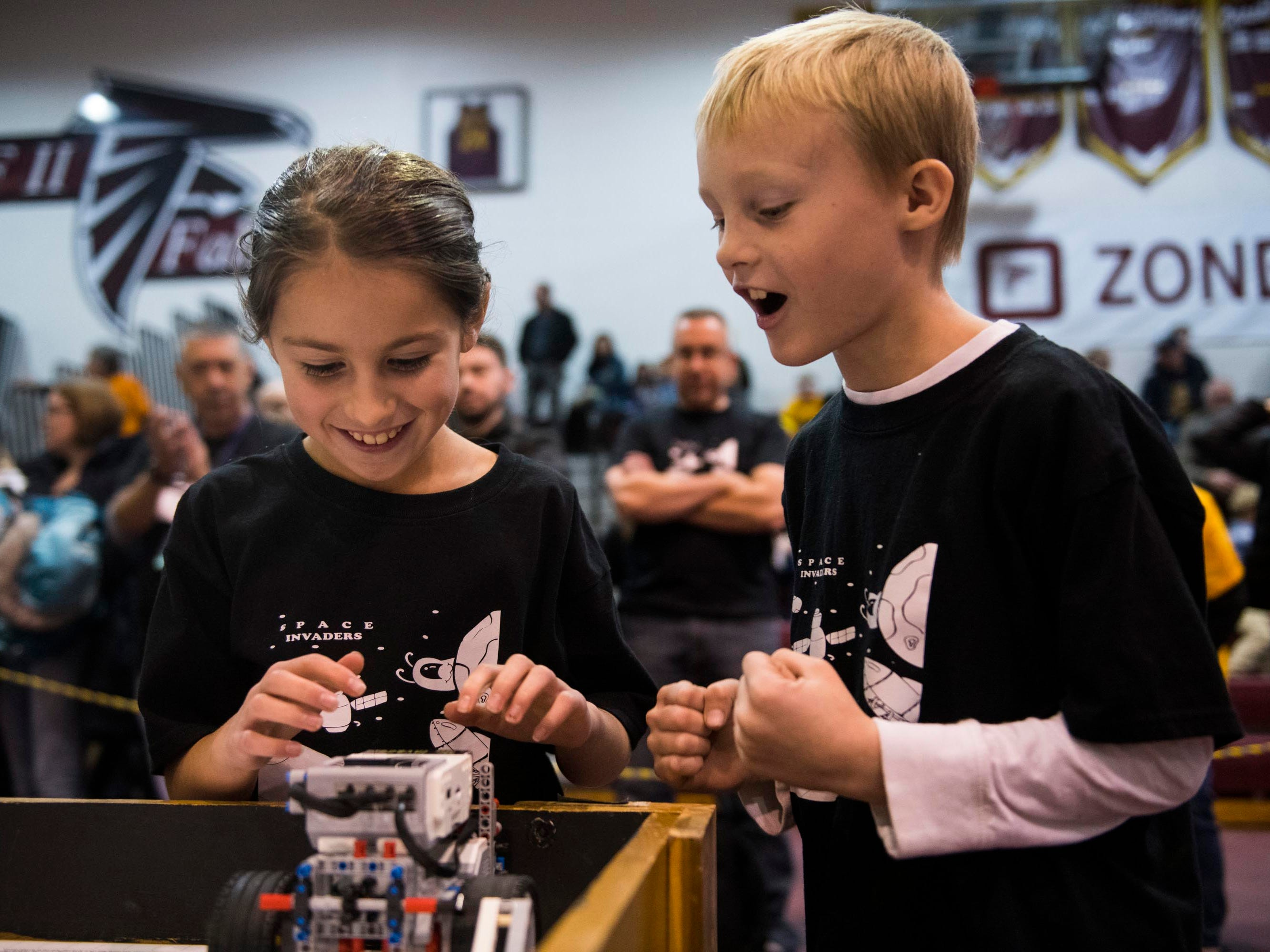 Paige Brinkey, 9, and Leo Klinger, 9, of Shelby Township, members of the Space Invaders robotics team, get ready to send off their robot for competition at the annual UCS ThunderQuest, a regional tournament for FIRST LEGO robotics teams, at Henry Ford II High School in Sterling Heights on Saturday.