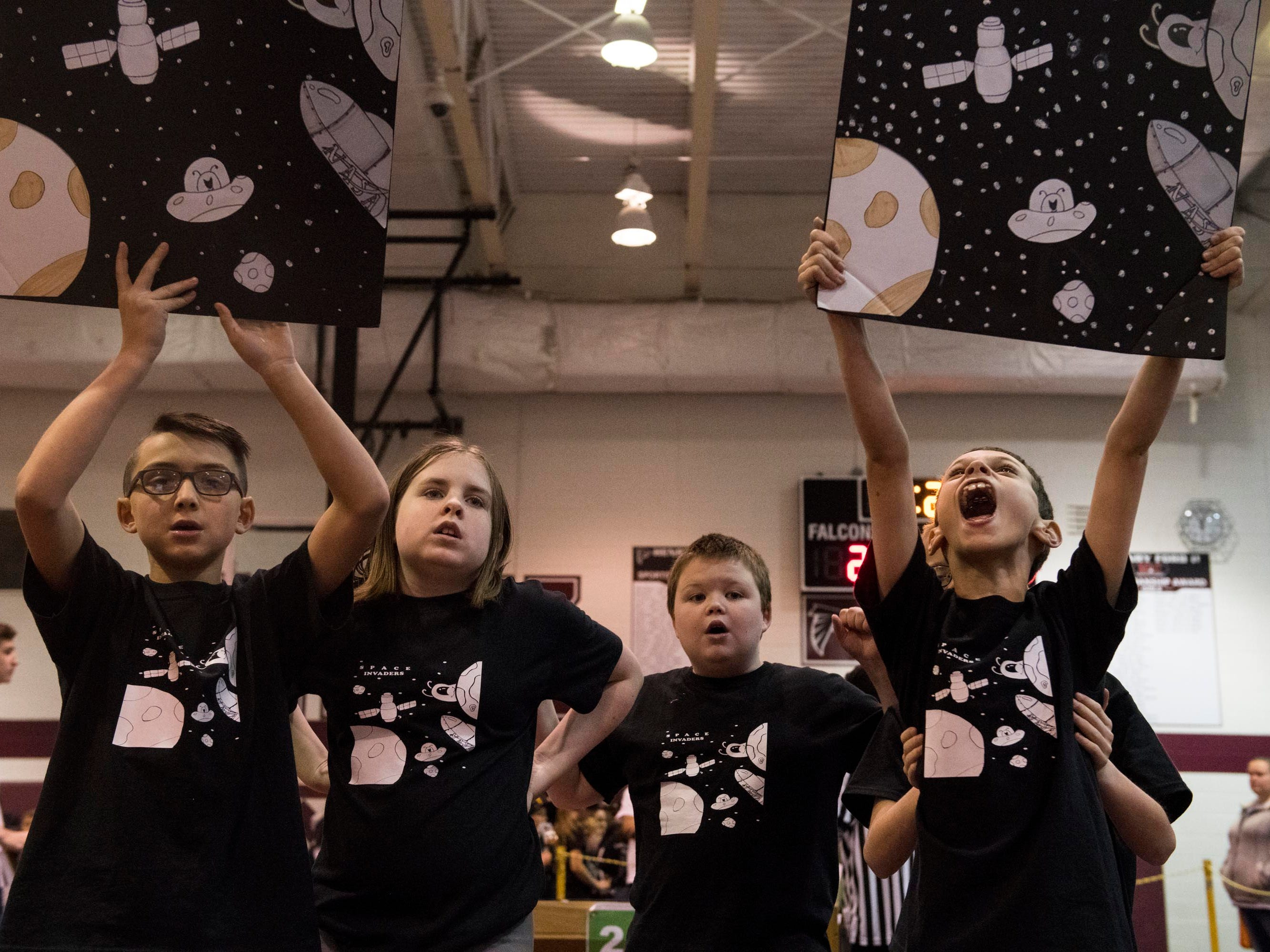 Members of the Space Invaders robotics team cheer for their teammates.