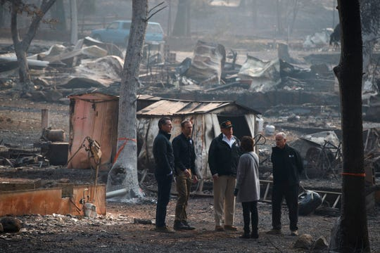 President Donald Trump talks with from left, Gov.-elect Gavin Newsom, FEMA Administrator Brock Long, Jody Jones, Mayor of Paradise, and California Gov. Jerry Brown during a visit to a neighborhood impacted by the wildfires, Saturday, Nov. 17, 2018, in Paradise, Calif.