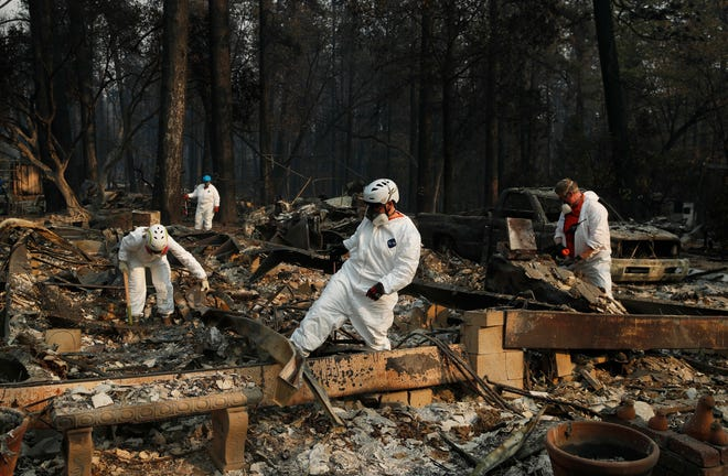 Search and rescue personnel search a home for human remains in the aftermath of the Camp fire, Friday, Nov. 16, 2018, in Paradise, Calif.