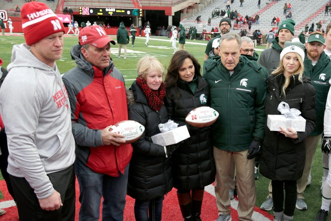 Nebraska head coach Scott Frost, from left; Gerald and Jill Foltz; Karen Sadler; Michigan State head coach Mark Dantonio; Katie Sadler participate in a midfield ceremony honoring late punters Mike Sadler and Sam Foltz.