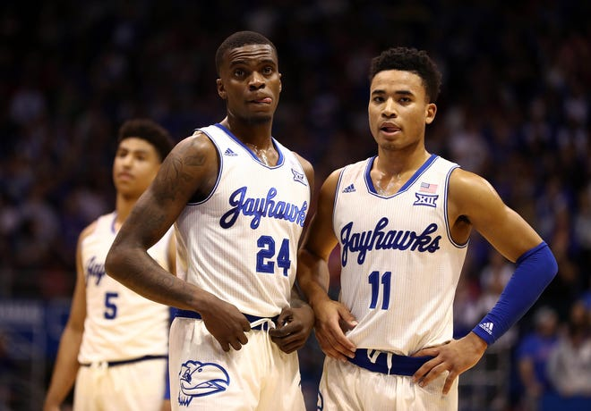 Lagerald Vick and Devon Dotson of the Kansas Jayhawks wait during a timeout.