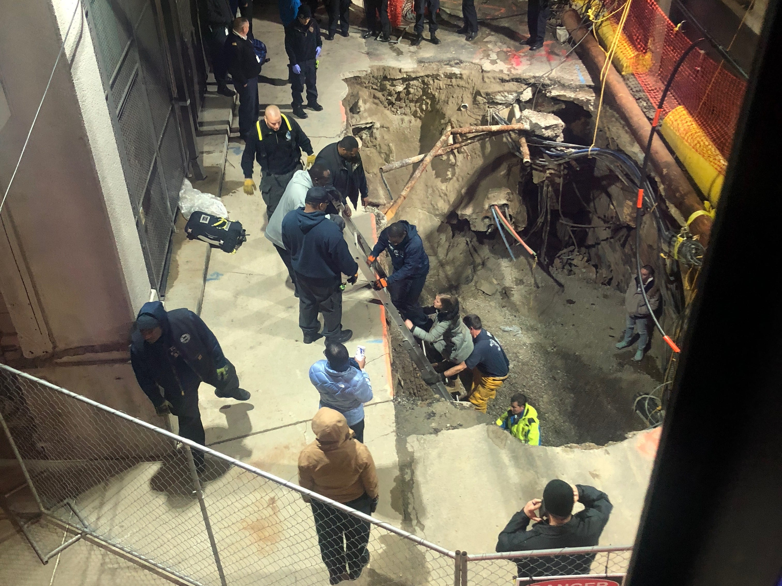 Woman rescued from sinkhole outside news building