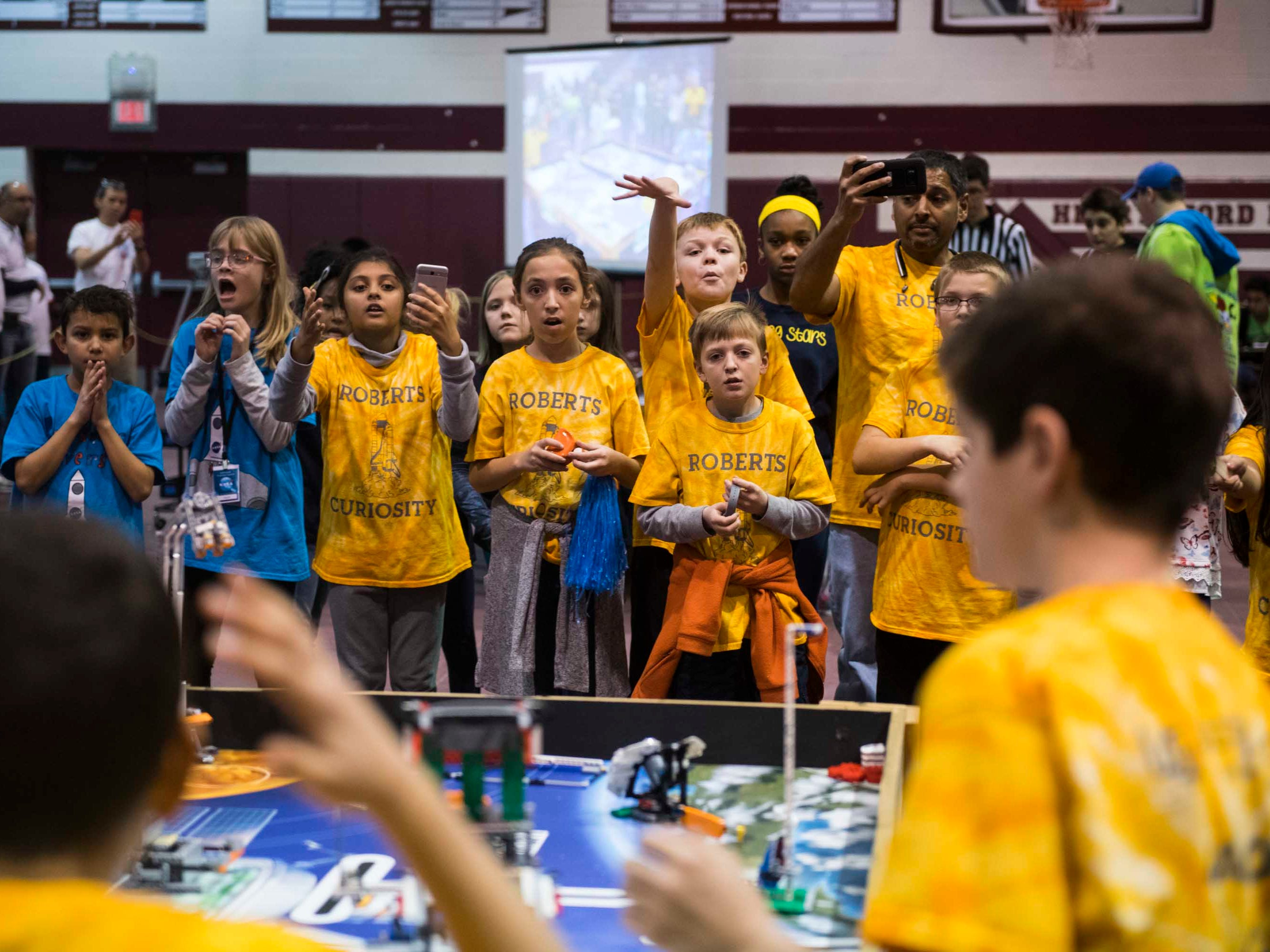Members of the Roberts Curiosity robotics team cheer for their teammates as they compete at ThunderQuest.