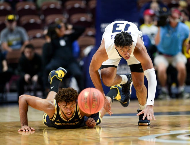 Michigan's Isaiah Livers and George Washington's DJ Williams chase down a loose ball.