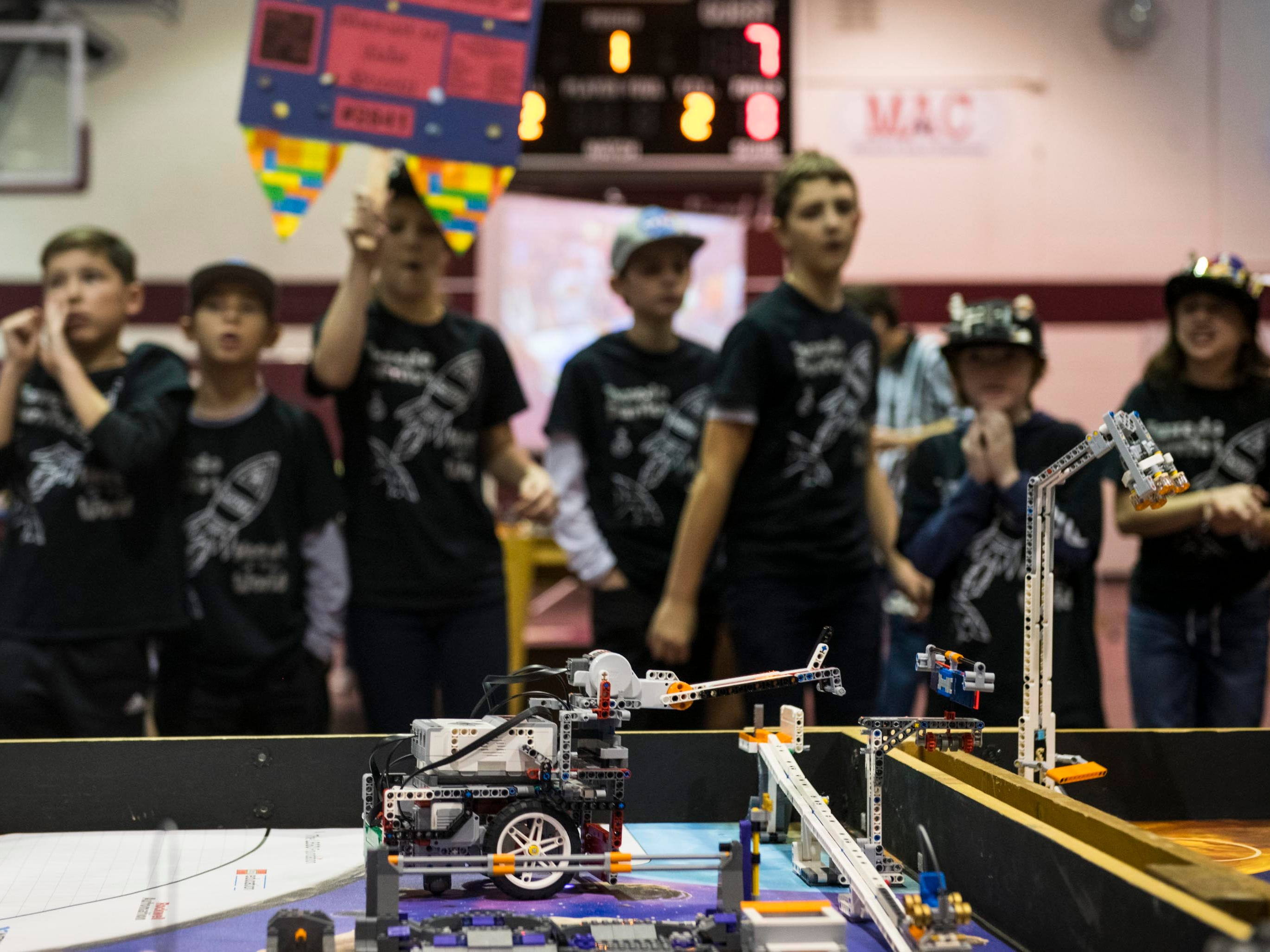 A robot built by the Tuxedo Purritos robotics team moves a solar panel piece during a competitive run.