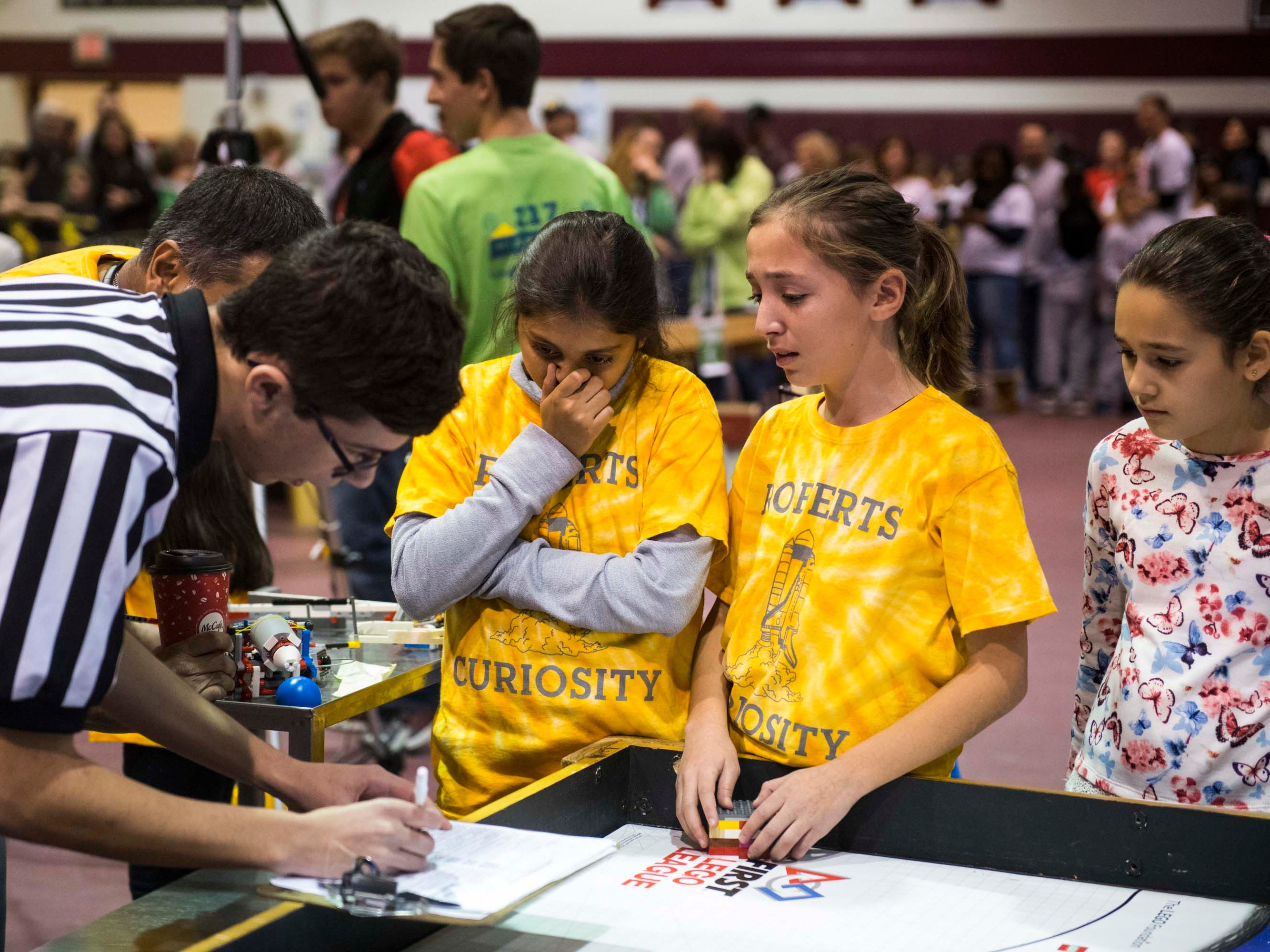 Aashna Moradia, 11, left, and Mikayla Pietraszkiewicz, 12, of the Roberts Curiosity robotics team wait to get their score after competing with their Lego robot.