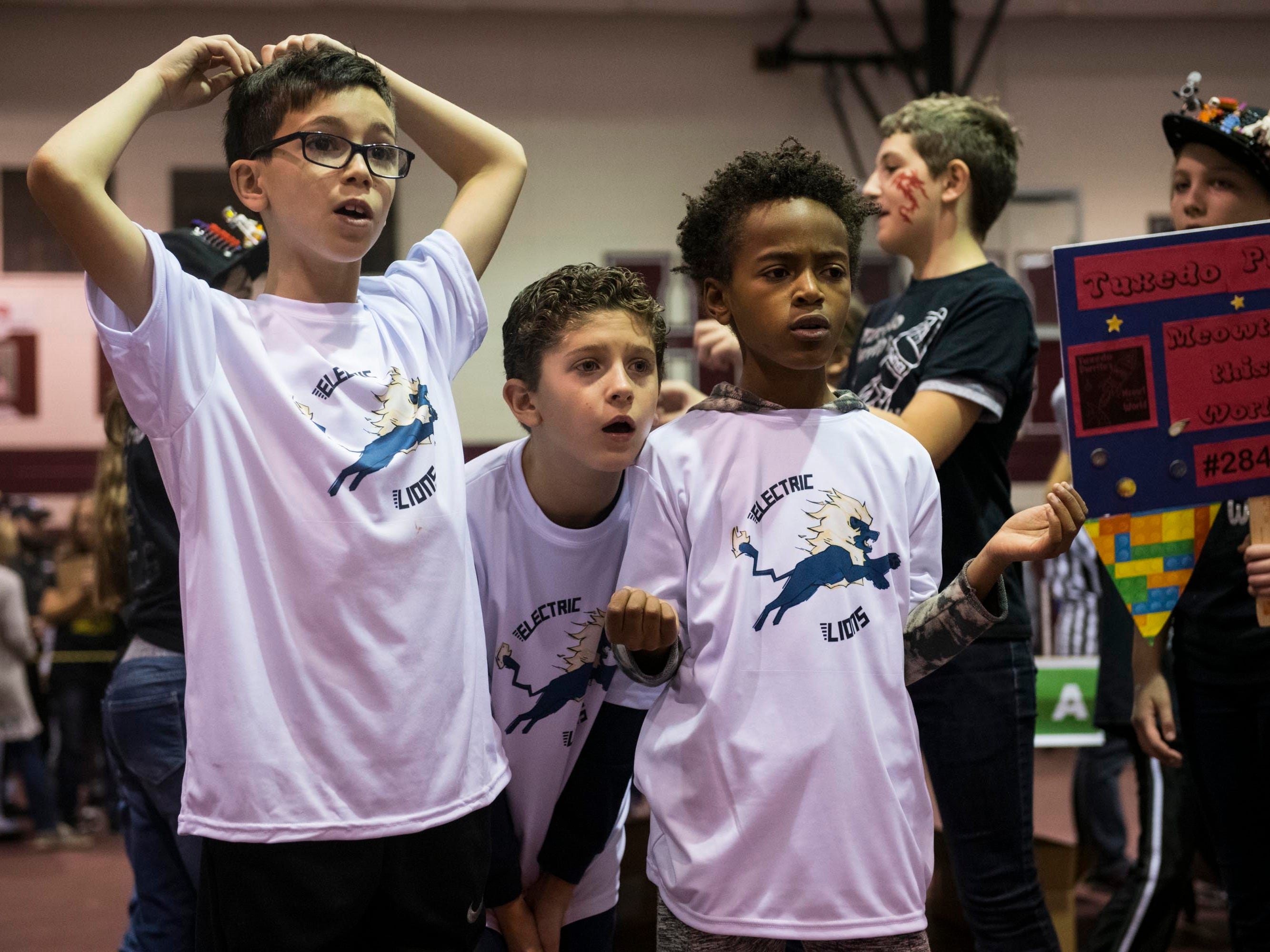 From left to right, AJ Priziola, 10, Sal Vitale, 10, and Xavier Smith, 10, watch anxiously as their teammates compete.