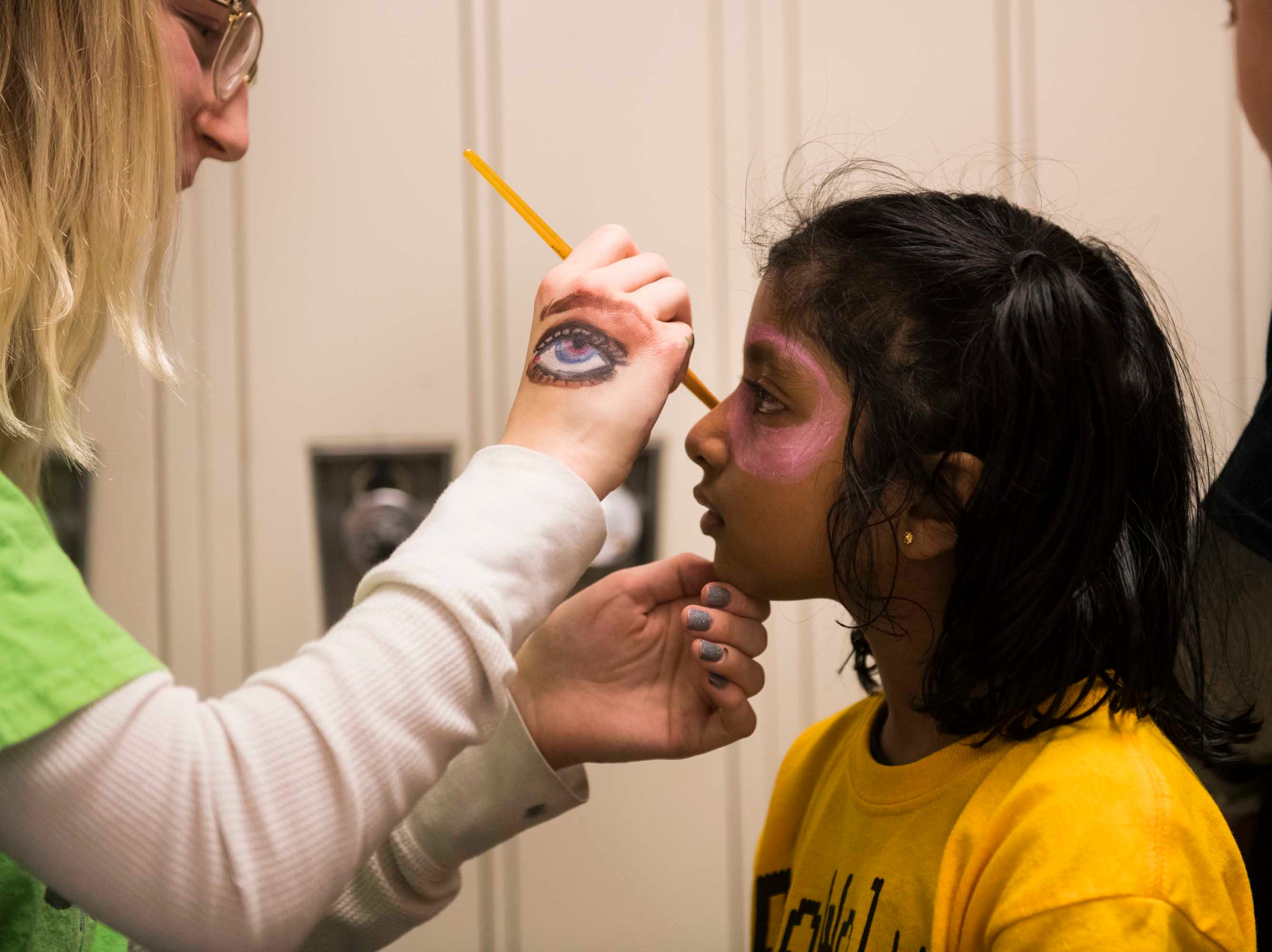 Keerthana C. 6, of Troy, a member of the Robowolves robotics team, gets her face painted by Bridgette Holtan, of Sterling Heights.