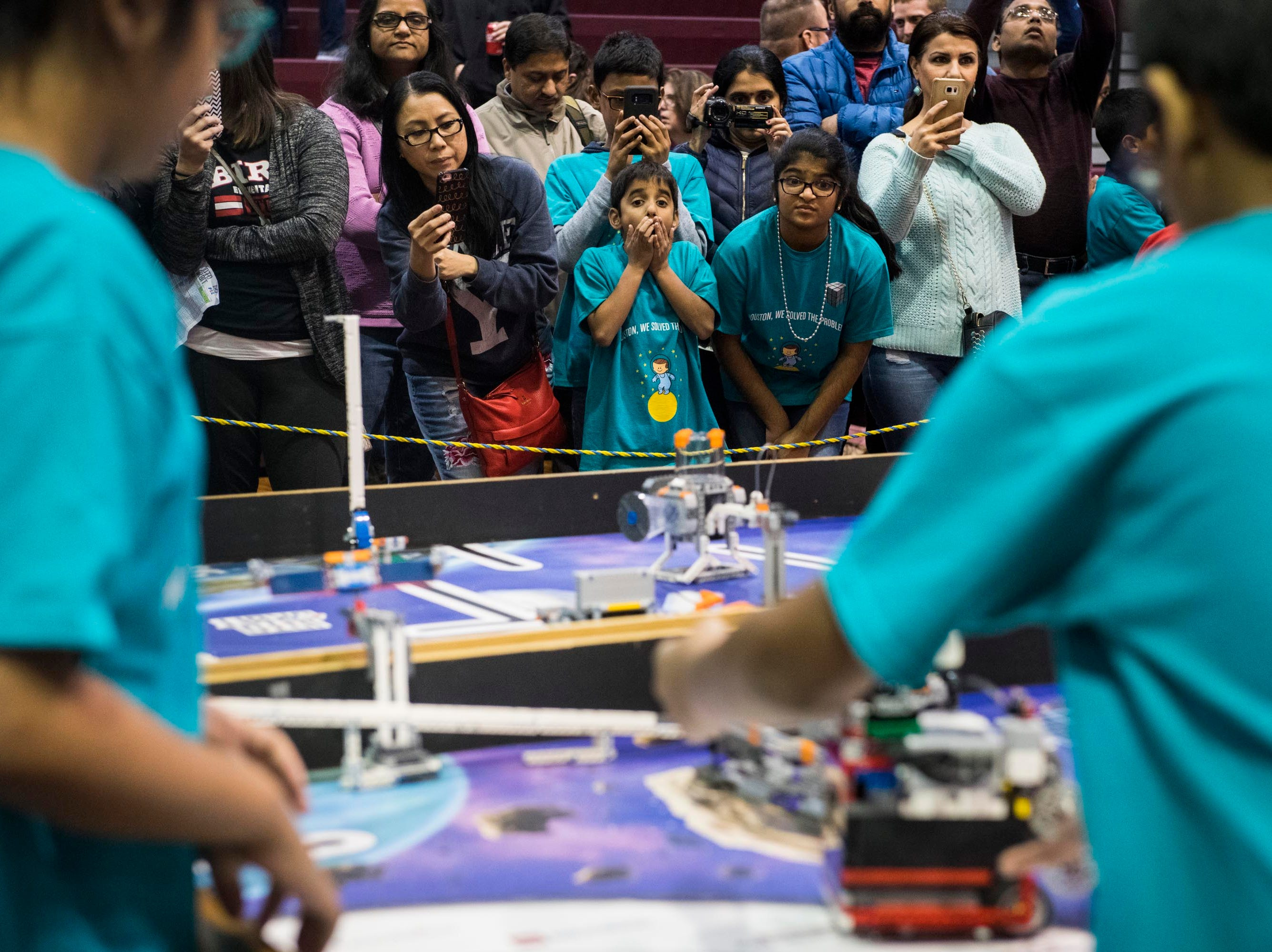 Guru Raja, 9, of Troy, left, and Aditi Gunukula, 10, of Troy, right, of the 'Houston, We Solved the Problem' robotics team nervously watch their teammates compete.