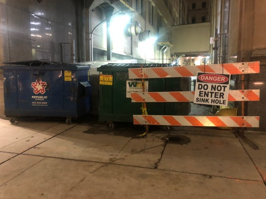 The alley off of Griswold downtown is blocked with dumpsters, a gate, fencing and a sign, warning of the sink hole