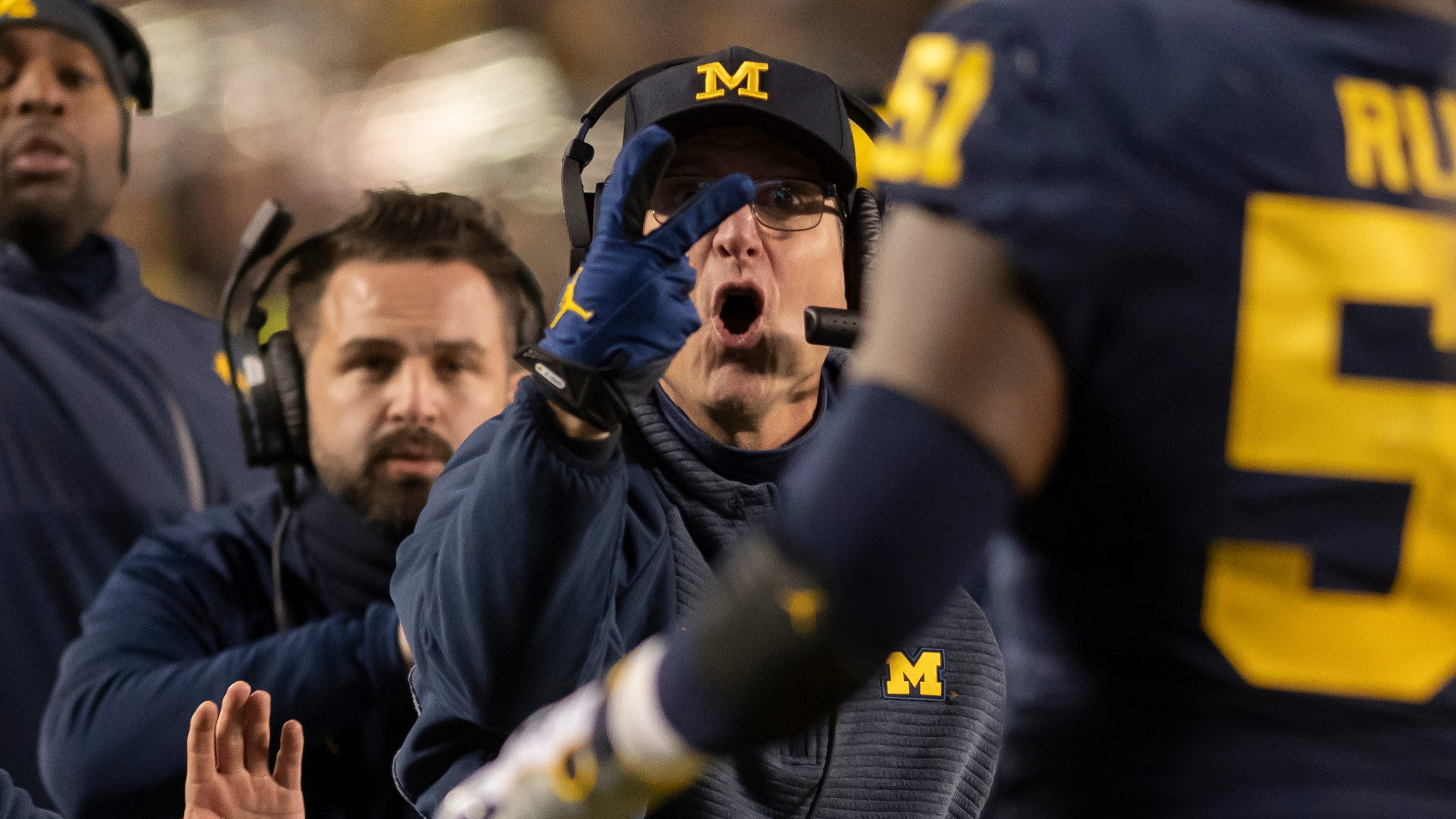 Michigan head coach Jim Harbaugh signals to his players to try for a two-point conversion after a touchdown in the second quarter.