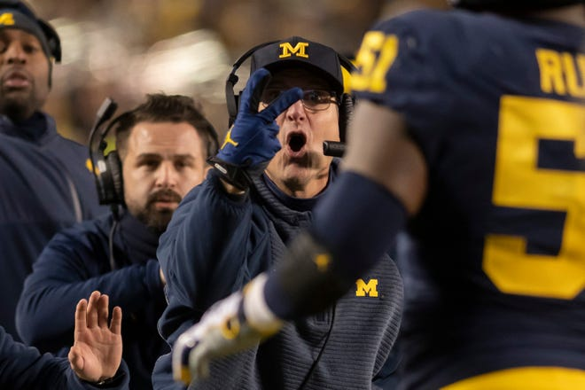 Michigan head coach Jim Harbaugh signals to his players to try for a two-point conversion after a touchdown in the second quarter on Saturday against Indiana.
