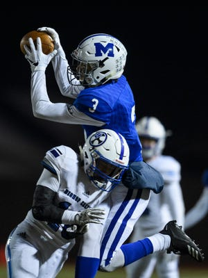 Memorial's Colton Pence catches a pass from Memorial's Michael Lindauer before falling out of bounds with Bishop Chatard's Jackson Sherby in the IHSAA Class 3A semistate championship at Enlow Field.