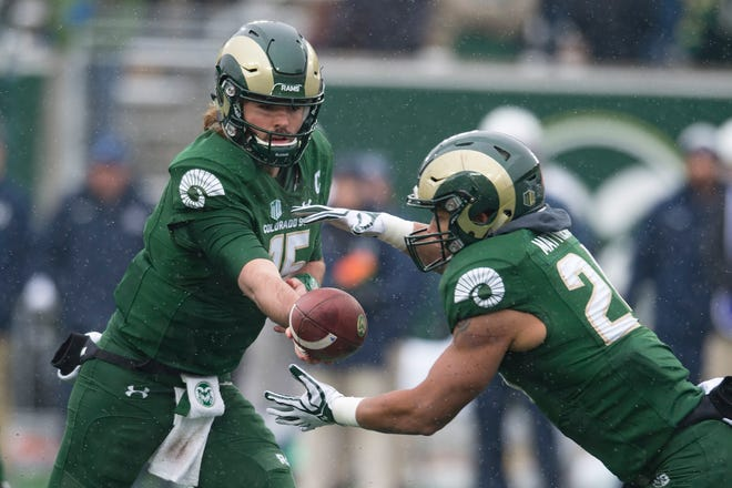 CSU quarterback Collin Hill hands the ball off to running back Izzy Matthews during a game against Utah State at Canvas Stadium on Saturday, November 17, 2018.