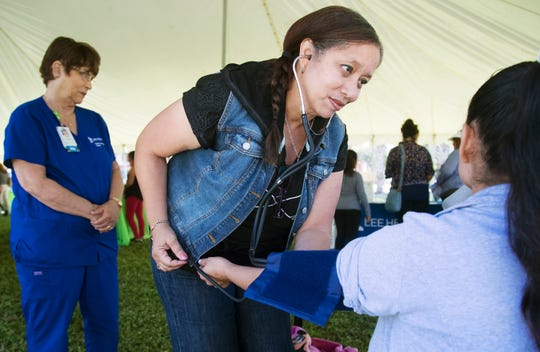 Frances Lopez, center, of Lee Health's Parish Nurse Program, was one of several health professionals conducting screenings during a health fair on Saturday at Schandler Hall Community Park in Fort Myers. The fairfeatured health screenings, activities and turkeys were given away for Thanksgiving. Nations Association Charities and Lee Health presented the event.