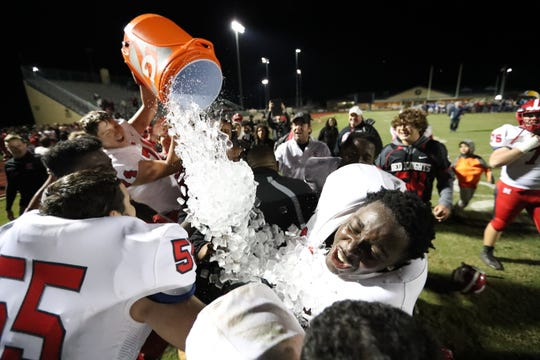 The North Fort Myers high school football coach is hit with a bucket of ice after the team defeated Charlotte 36-20 during week 2 of state playoffs on Friday, Nov. 16, 2018.