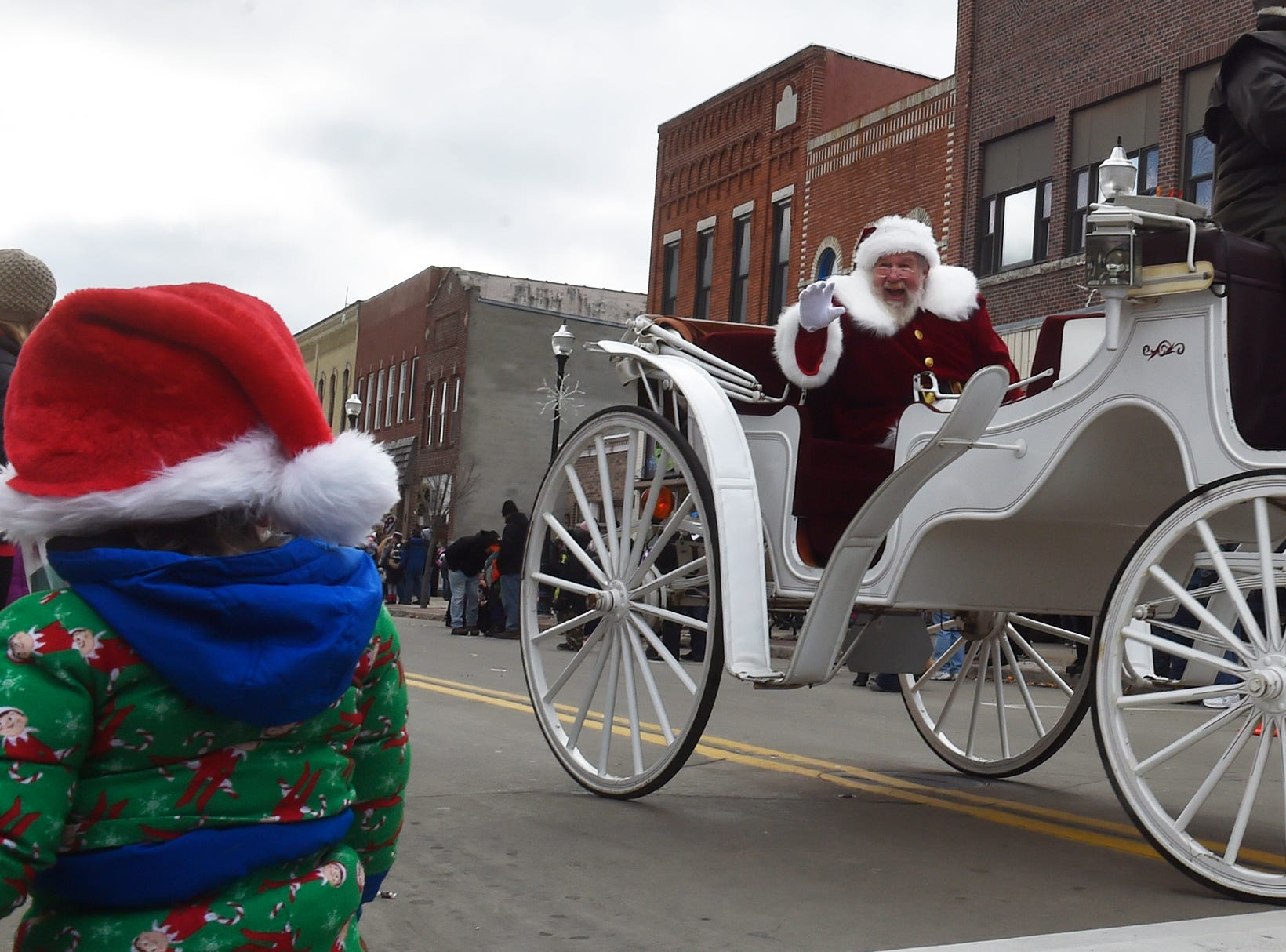 Santa gets the attention of a Santa-hat toddler while riding aboard a horse-drawn carriage at the Christmas By The Bay parade on Saturday, Nov. 17, 2018, in Sturgeon Bay. Tina M. Gohr/USA TODAY NETWORK-Wisconsin