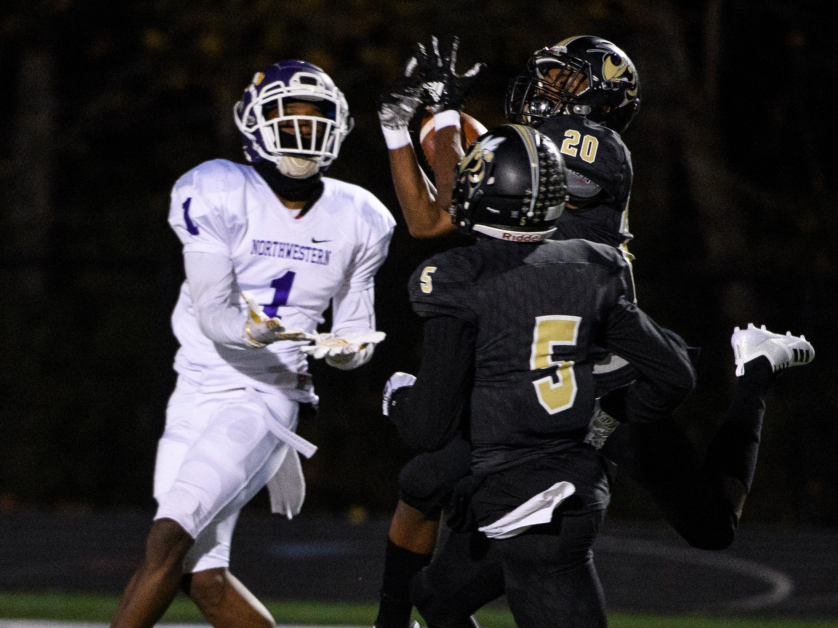 T.L Hanna's Ja'Nike Truesdale (20) intercepts a pass meant for Northwestern's Jamario Holley (1) on Friday, Nov. 16, 2018.