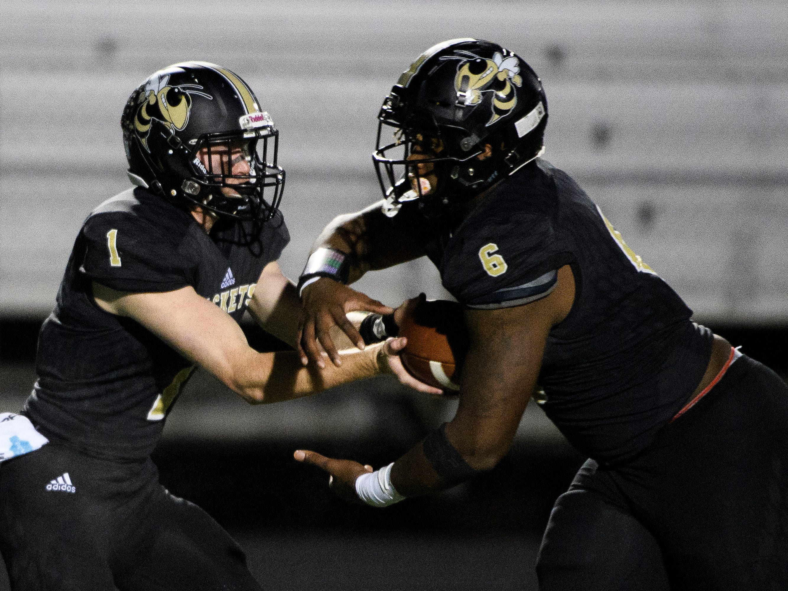 T.L. Hanna's Alex Meredith (1) hands the ball off to Zacch Pickens (6) during their game against Northwestern on Friday, Nov. 16, 2018.