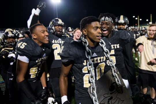 T.L. Hanna teammates celebrate with Ja'Nike Truesdale (20) after he is awarded the turnover chain for intercepting a pass in the Yellow Jackets' rout of Northwestern on Friday night.