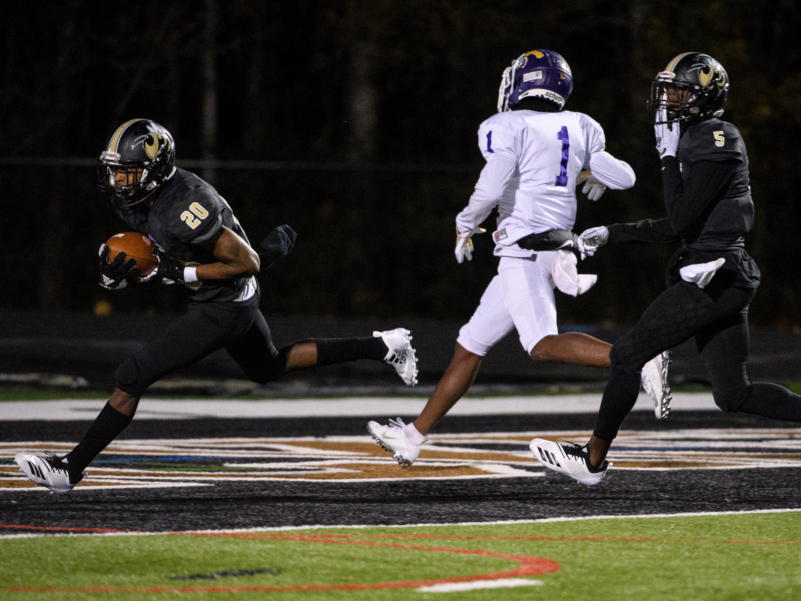 T.L Hanna's Ja'Nike Truesdale (20) runs after he intercepts a pass meant for Northwestern's Jamario Holley (1) on Friday, Nov. 16, 2018.