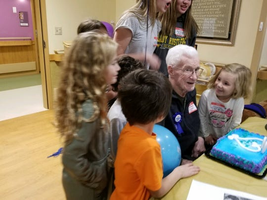 The great-grandchildren of Ray B. Brady surround him at his recent 100th birthday party.