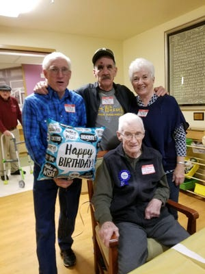 Ken, Branch and DeeAnna stand behind their father, Ray B. Brady, at his recent 100th birthday part in Great Falls.