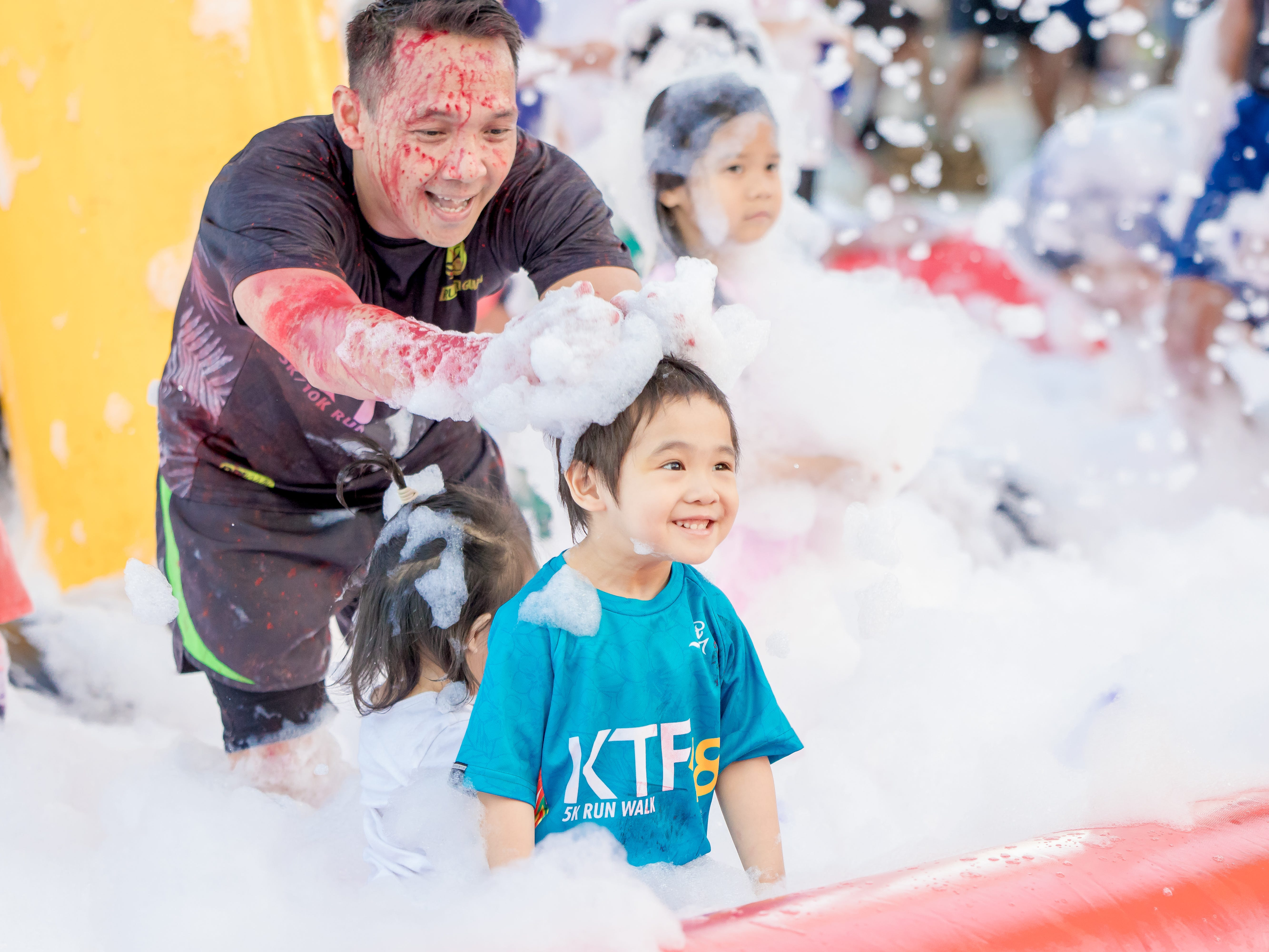"""Kerwin Baldemor and his son Louie Baldemor,3 years old, have fun at the bubble foam pit setup during the 13th Annual Triple J Family 10K/5K Run themed the """"Bubble Color Run"""" held  at Tripple J Complex in Tamuning on Nov.17.Virgilio Valencia /For Pacific Daily News"""