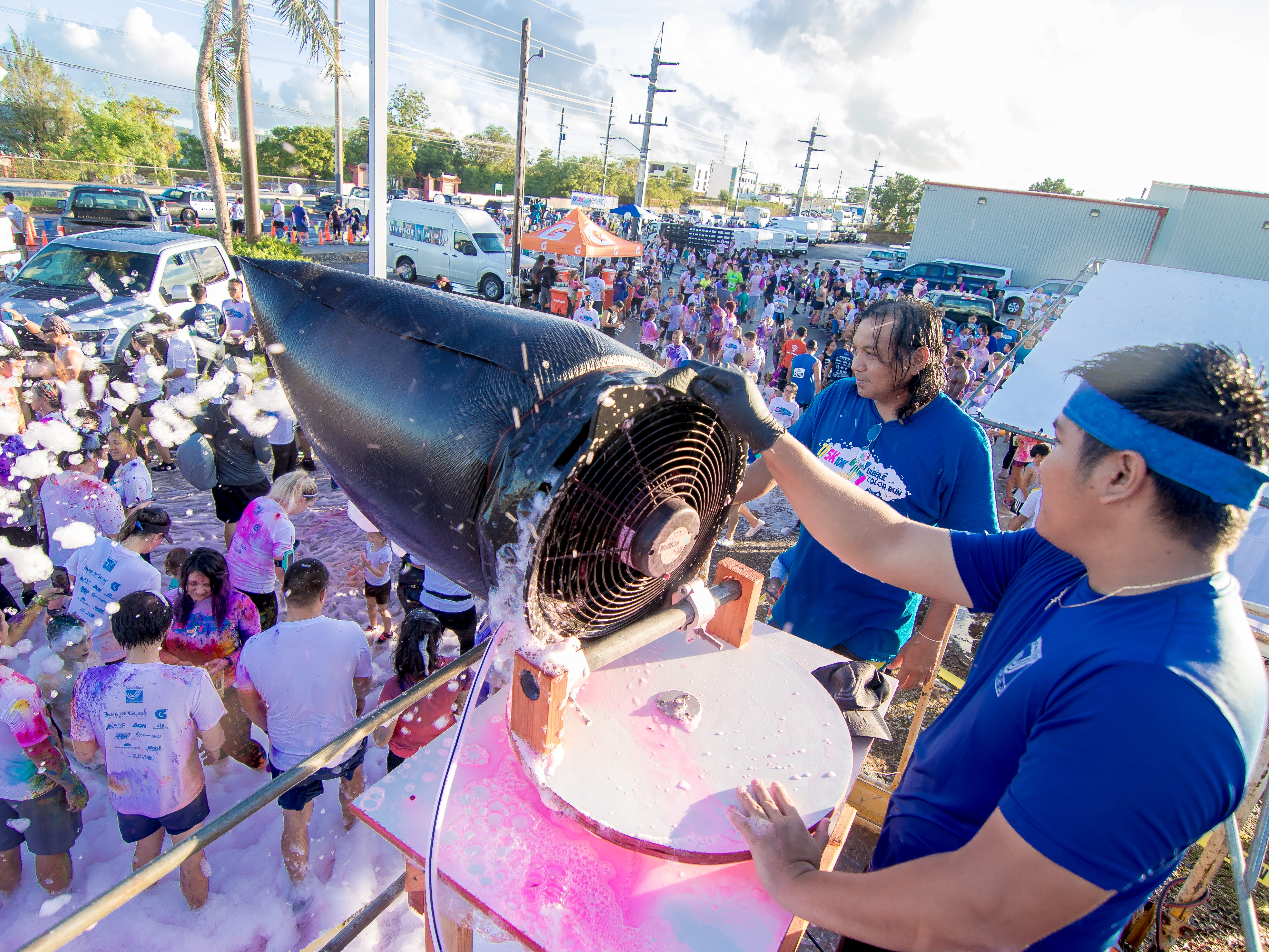 """Anthony Calip operates the bubble foam sprayer as his coworker Anthony Villanueva looks on during the 13th Annual Triple J Family 10K/5K Run themed the """"Bubble Color Run"""" held  at Tripple J Complex in Tamuning on Nov.17.Virgilio Valencia /For Pacific Daily News"""