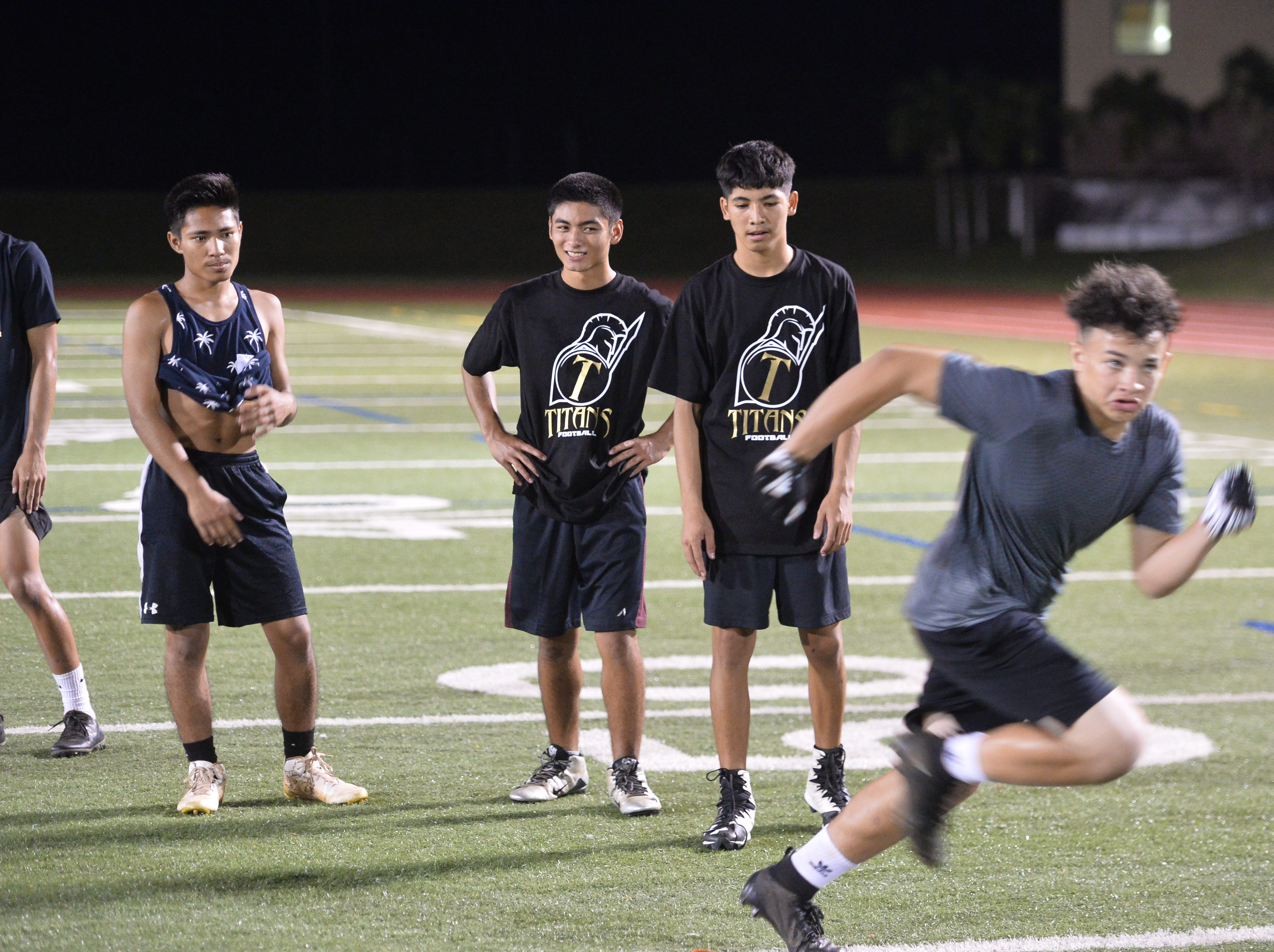 Football players wait their turn to run drills during the College Football Showcase and Combine Nov. 15 at Guam High.